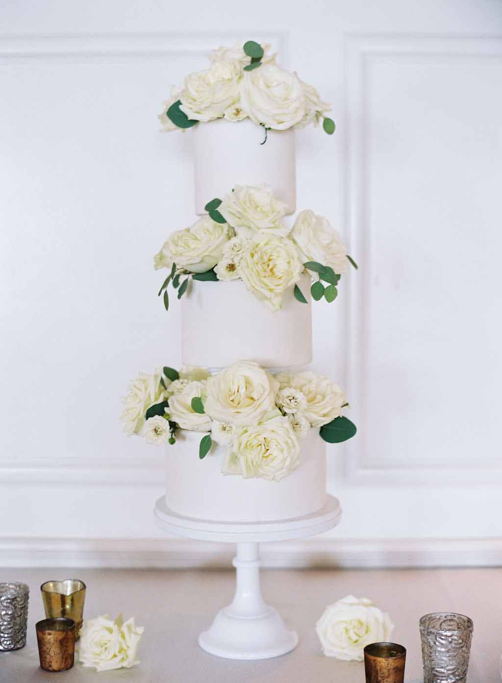three tiered cake decorated with white roses and greenery