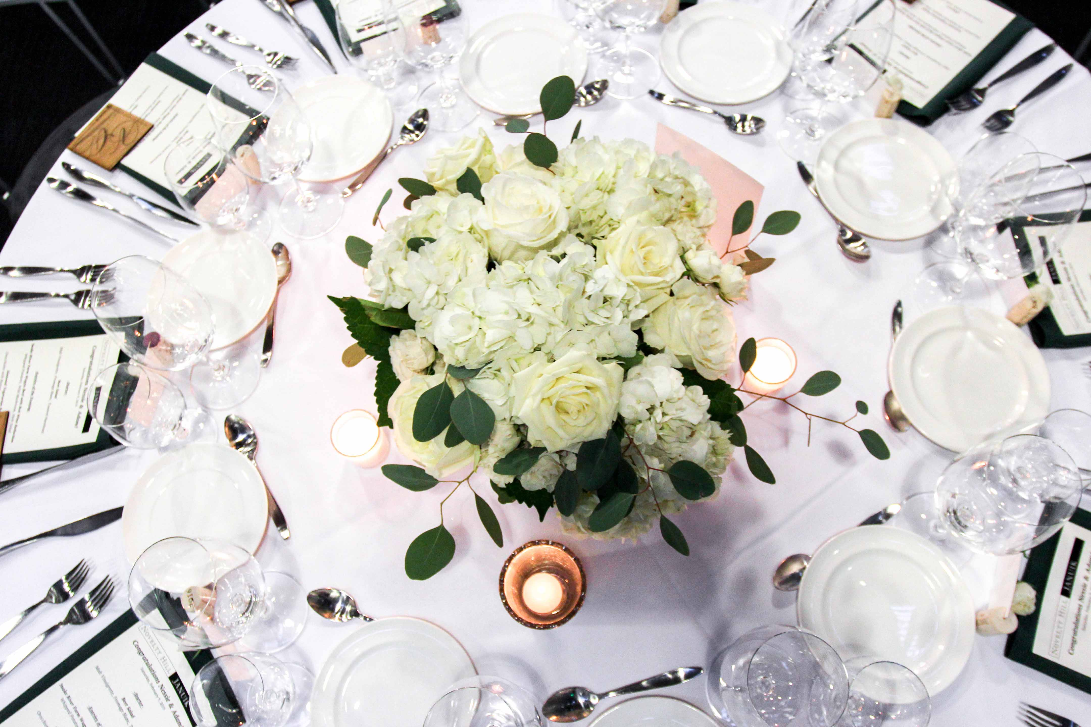 birds-eye view of round reception table with white centerpiece and candles