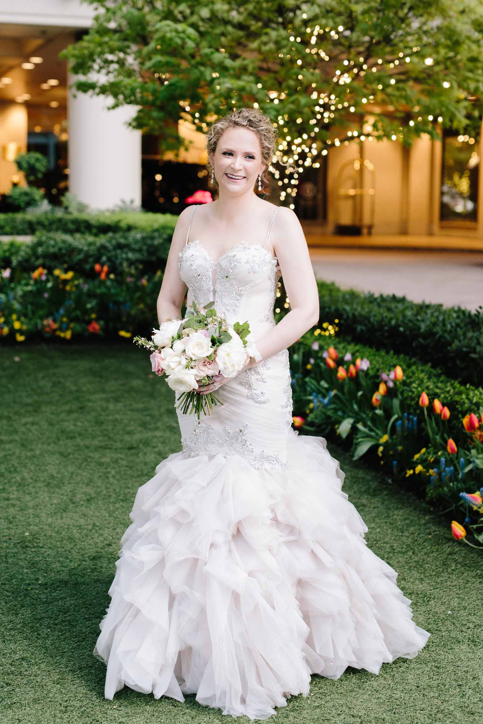 Bride dressed in white dress, holding spring garden bouquet on lawn outside hotel