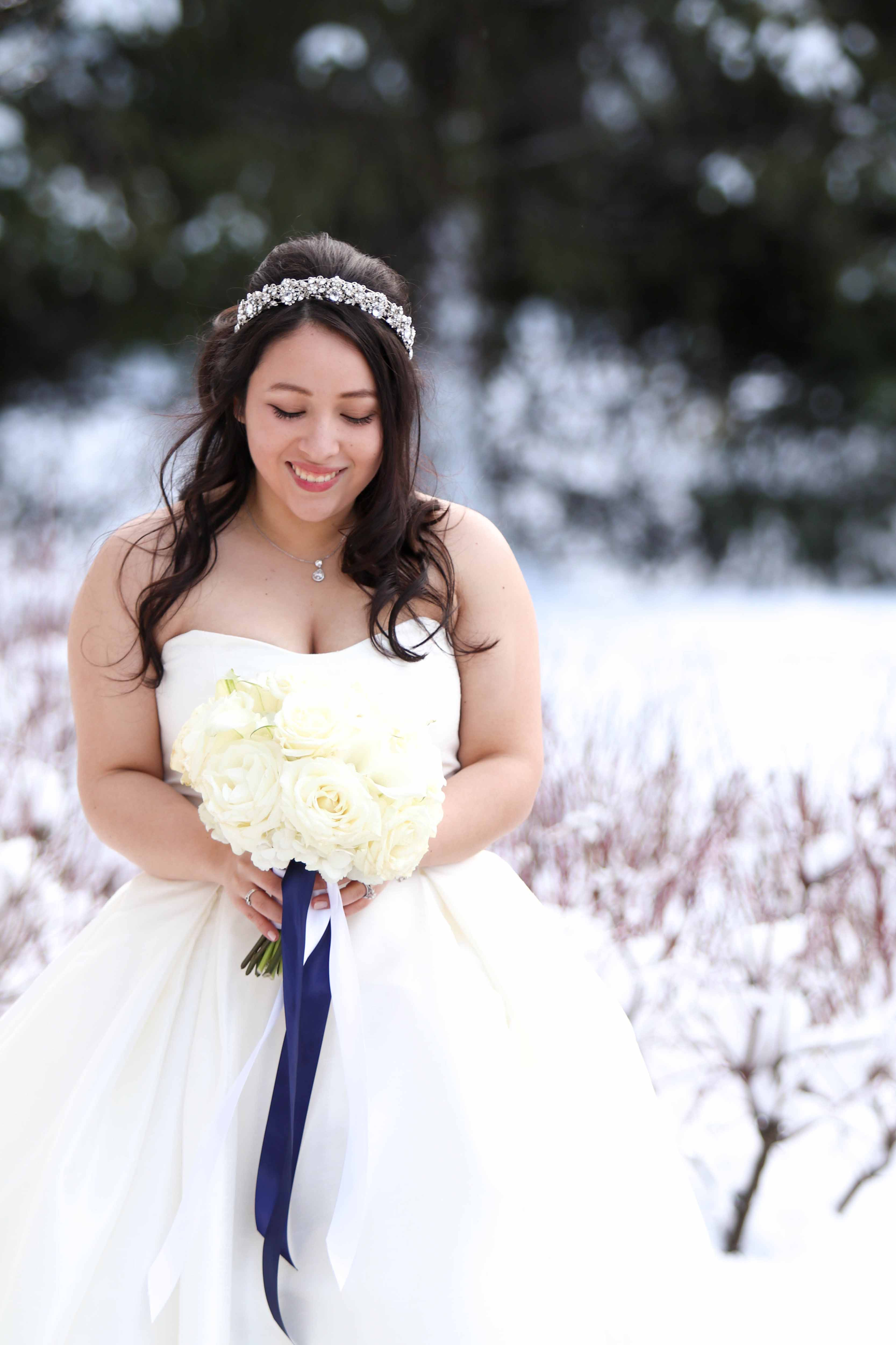 bride in white dress with white bouquet standing in snow