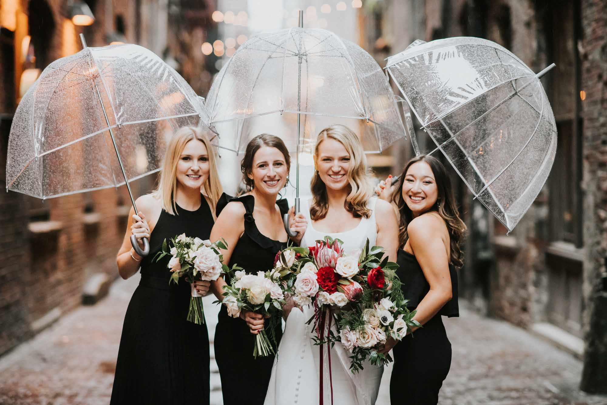 Bride and bridemaids pose under clear umbrellas