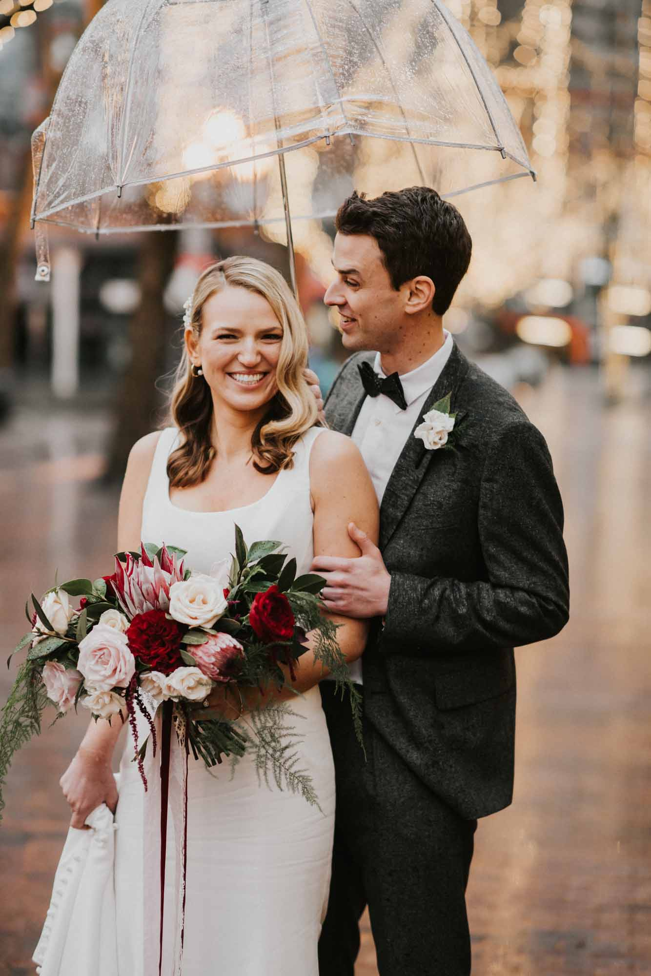 bride and groom under umbrella with wedding bouquet
