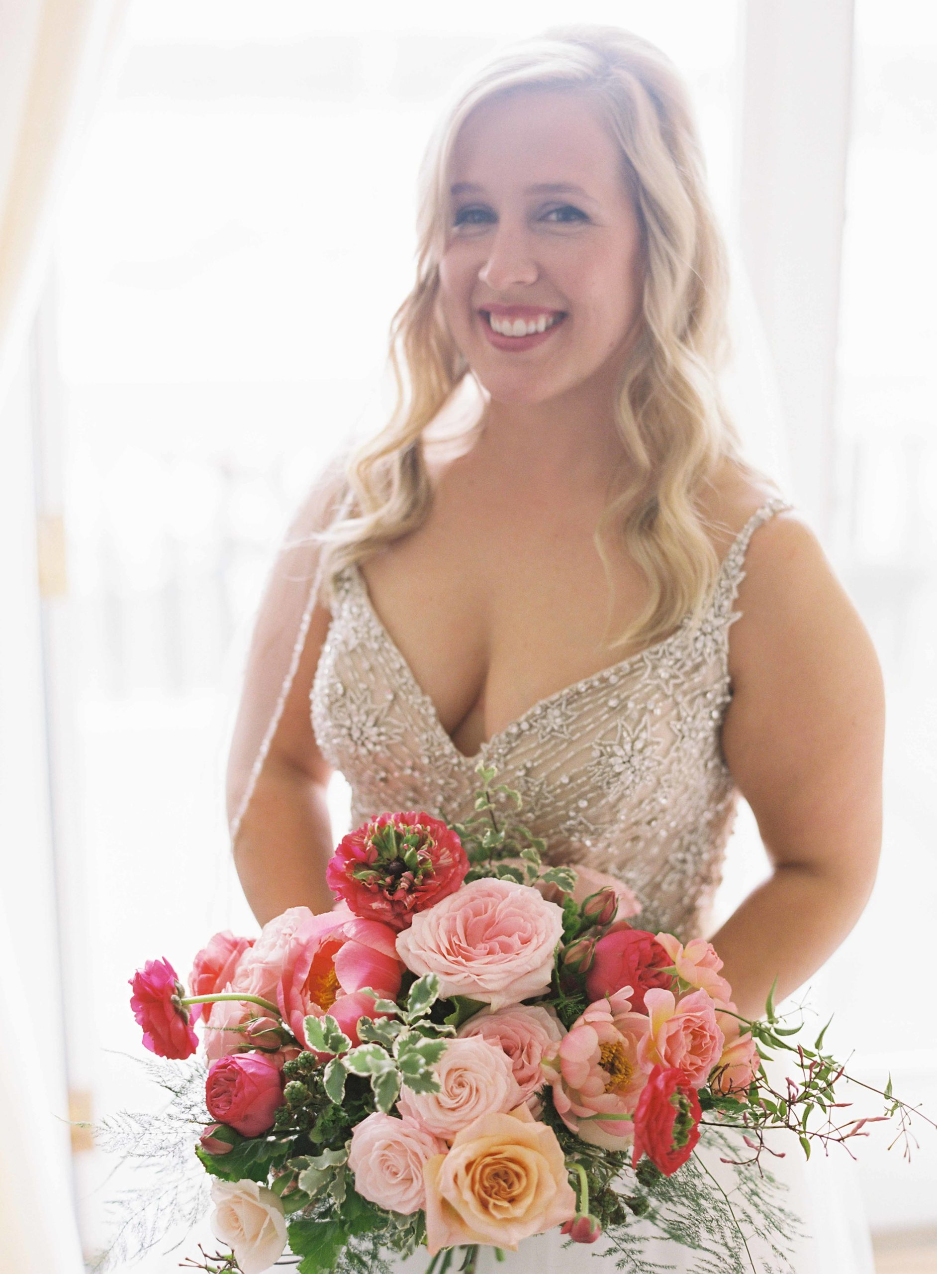 Hot pink and peach wedding bouquet held by smiling bride - Seattle Wedding Flowers by Flora Nova Design; Hot pink and peach wedding at Roche Harbor Resort