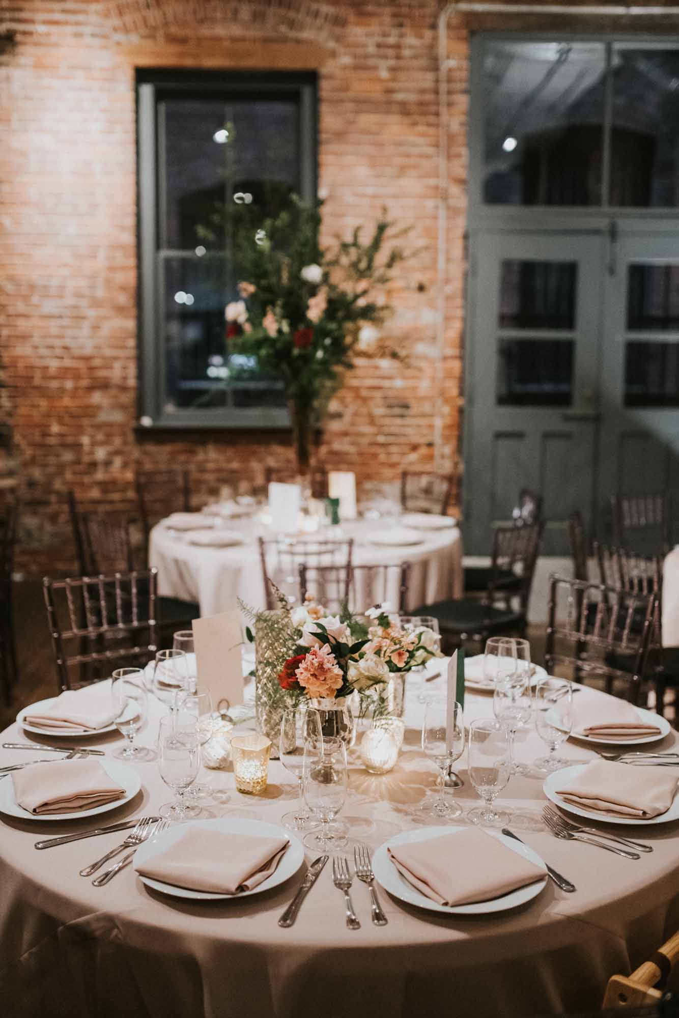 wedding reception tables in brick room