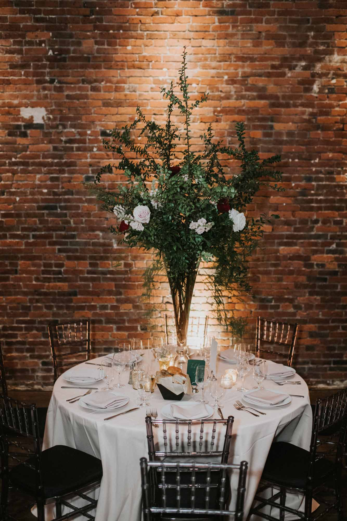 Tall greenery centerpiece on wedding reception table