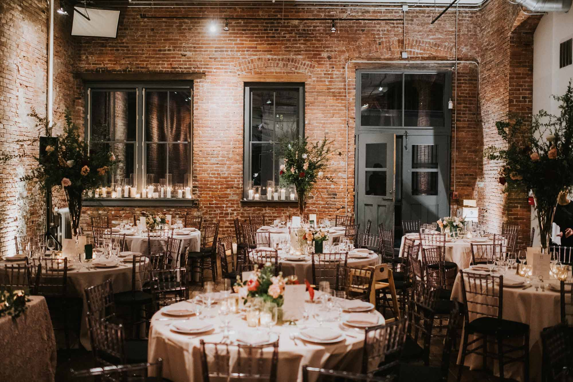 wedding reception with round tables and brick walls