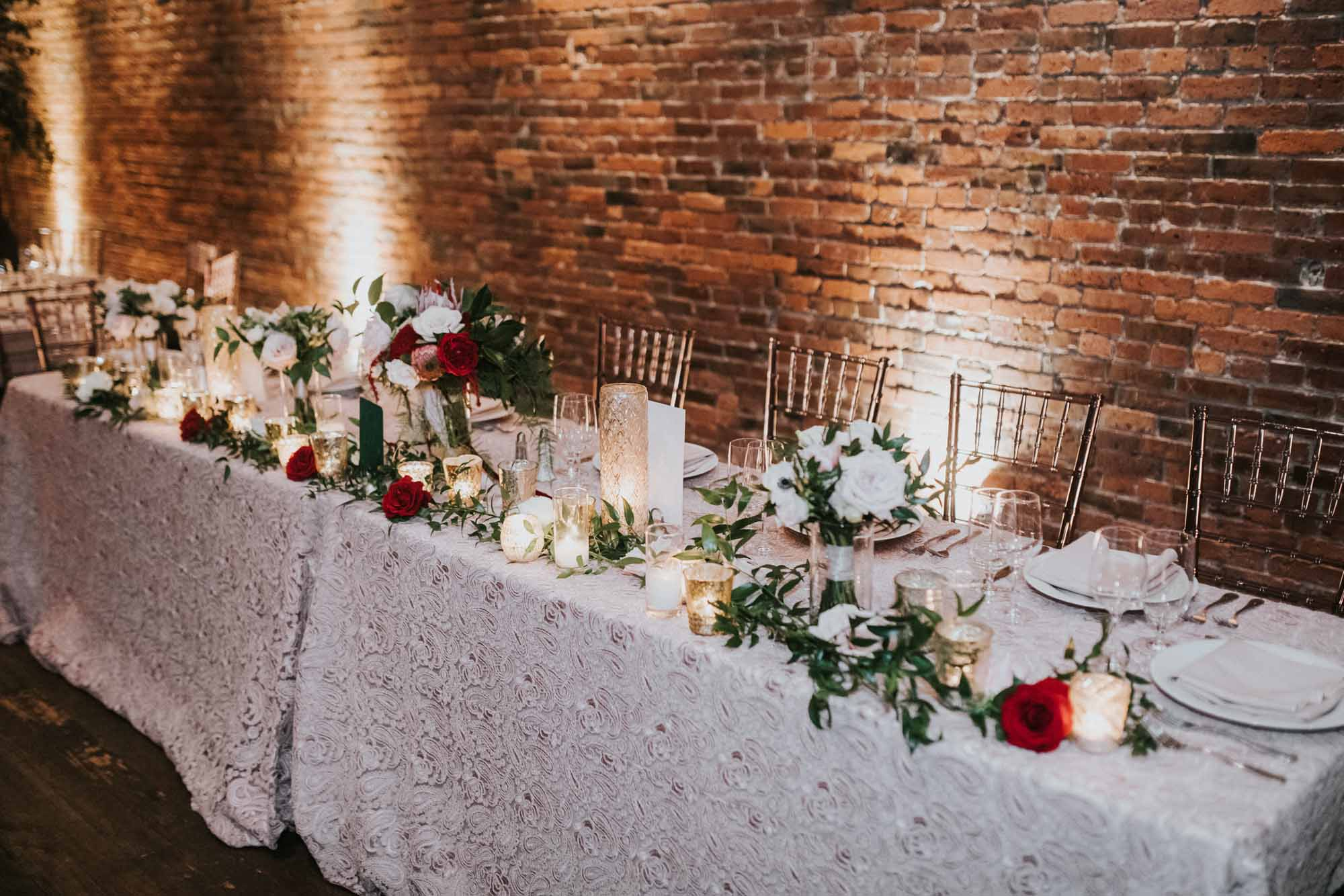 Head table with candles, flowers, and bouquets