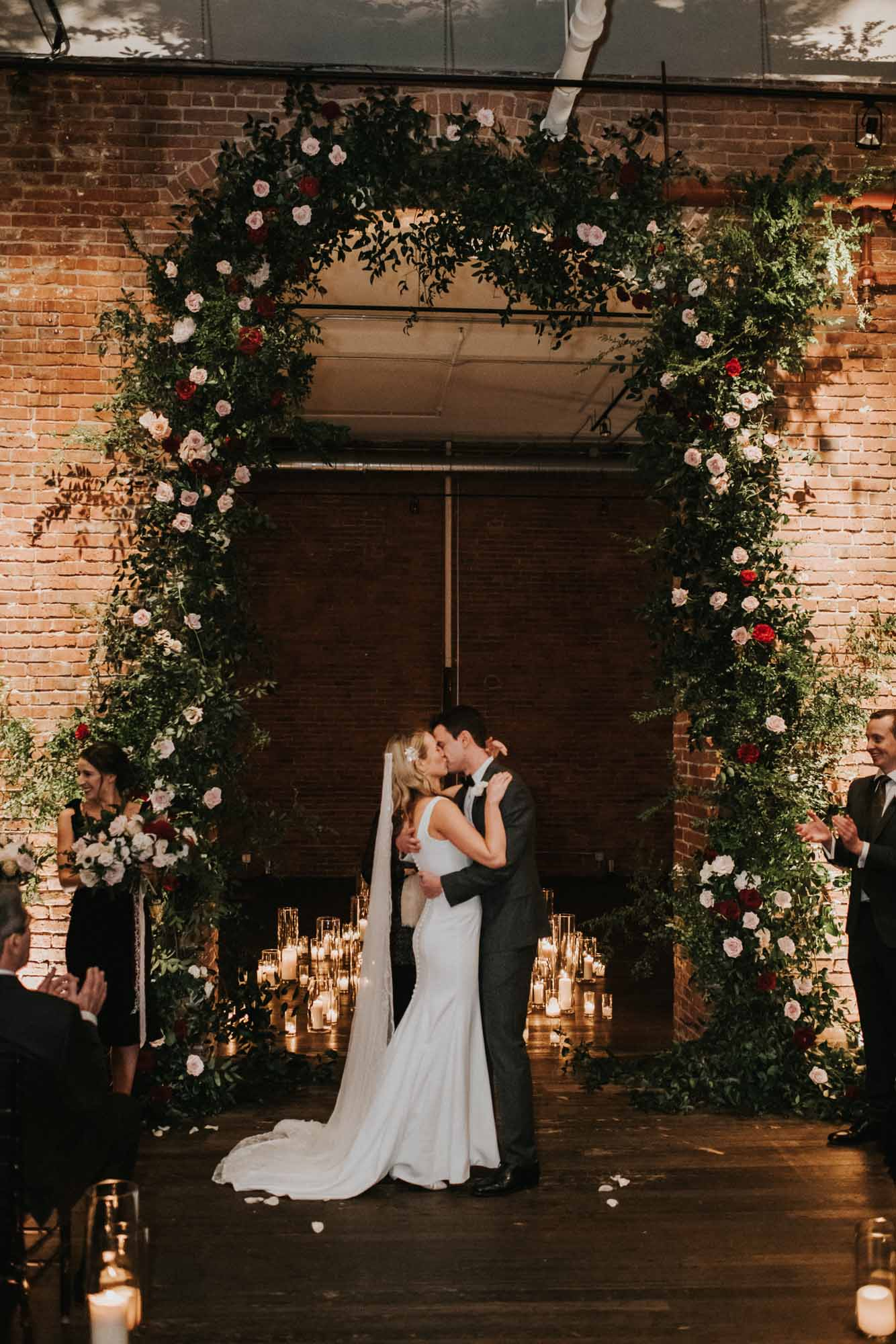 bride and groom kiss after ceremony under tall greenery arch