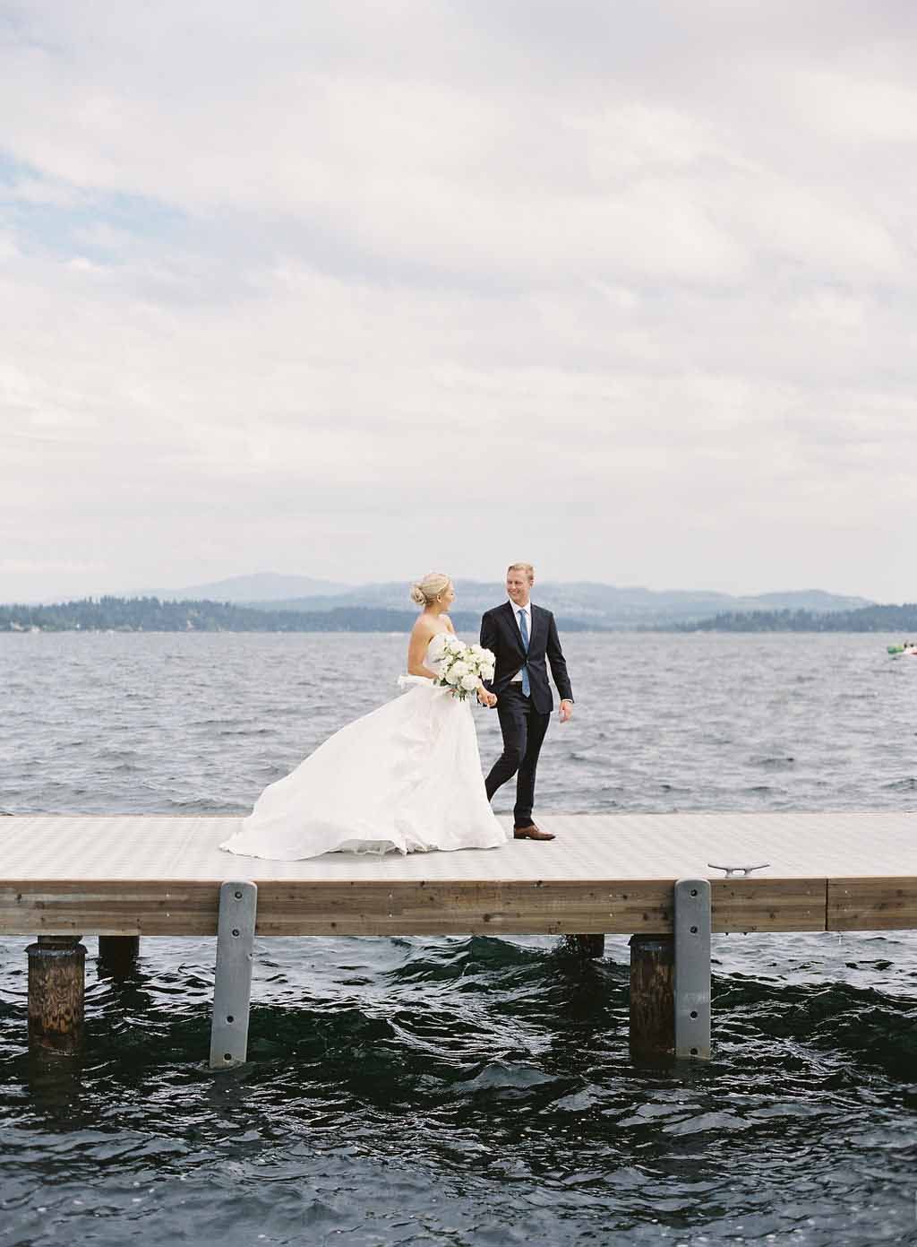 bride and groom walk along the dock at the Seattle Tennis Club