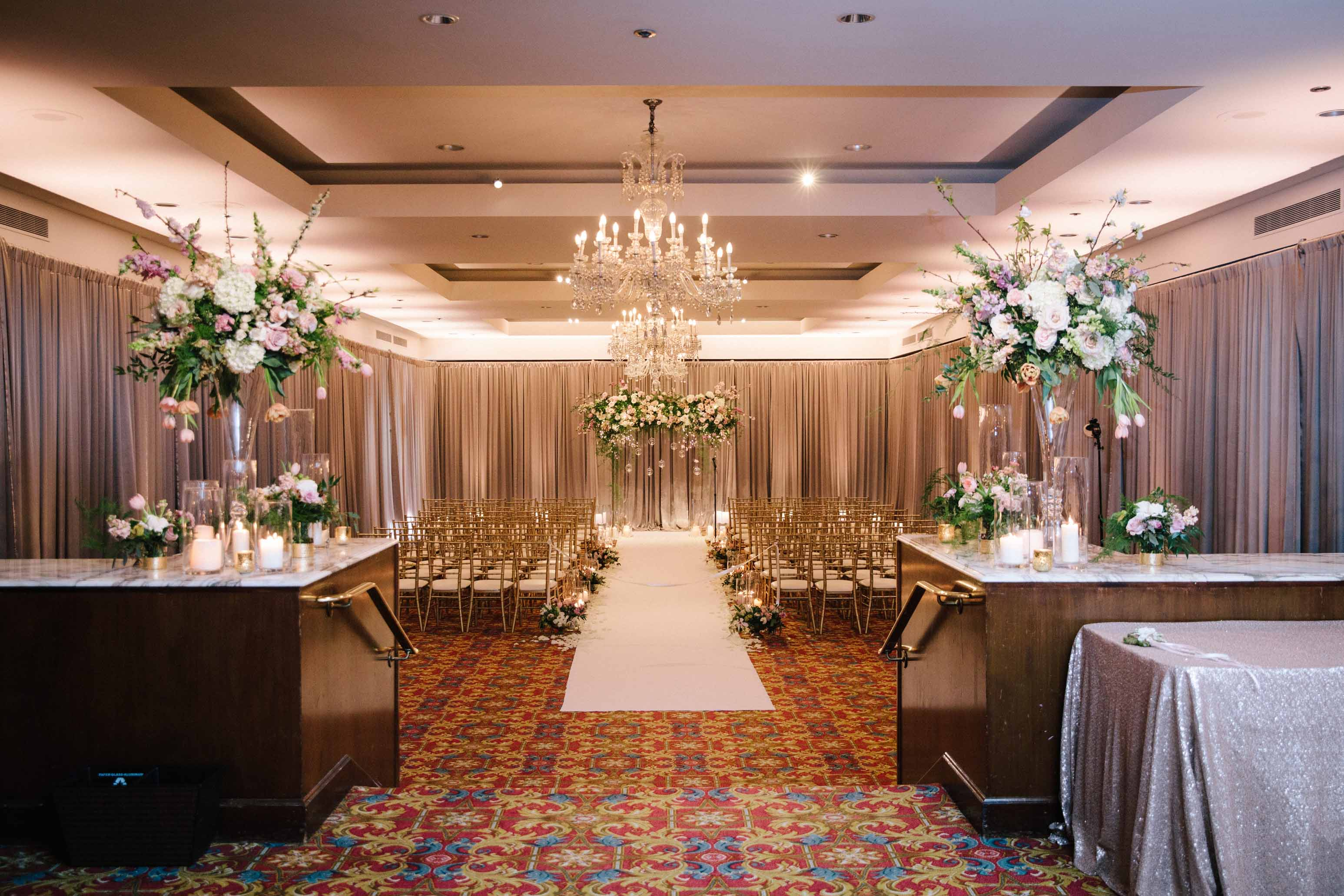 Wedding ceremony in hotel ballroom with ceremony arch, candles, and two large floral arrangements