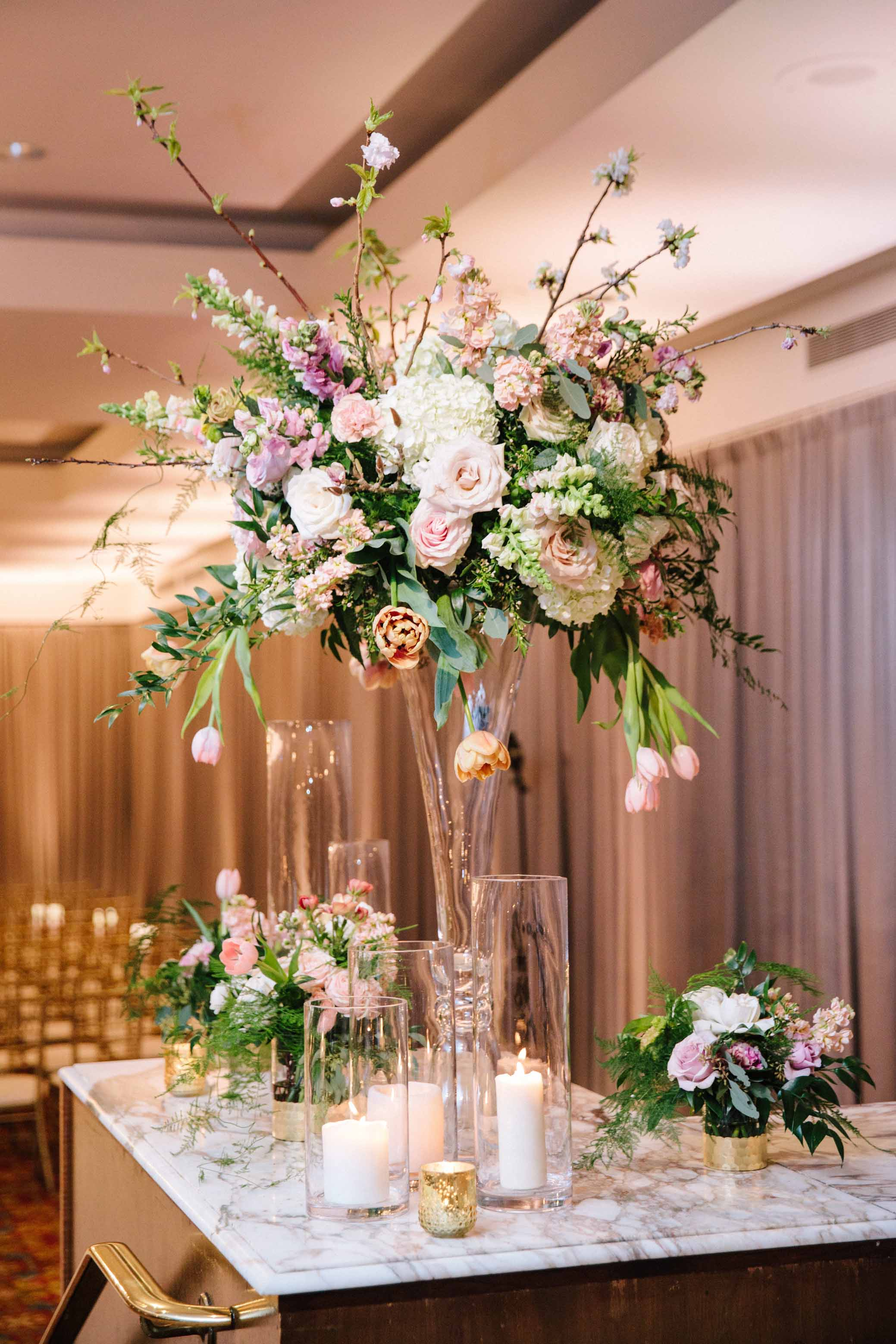Large spring garden centerpiece in pink and cream on tall crystal vase surrounded by candles