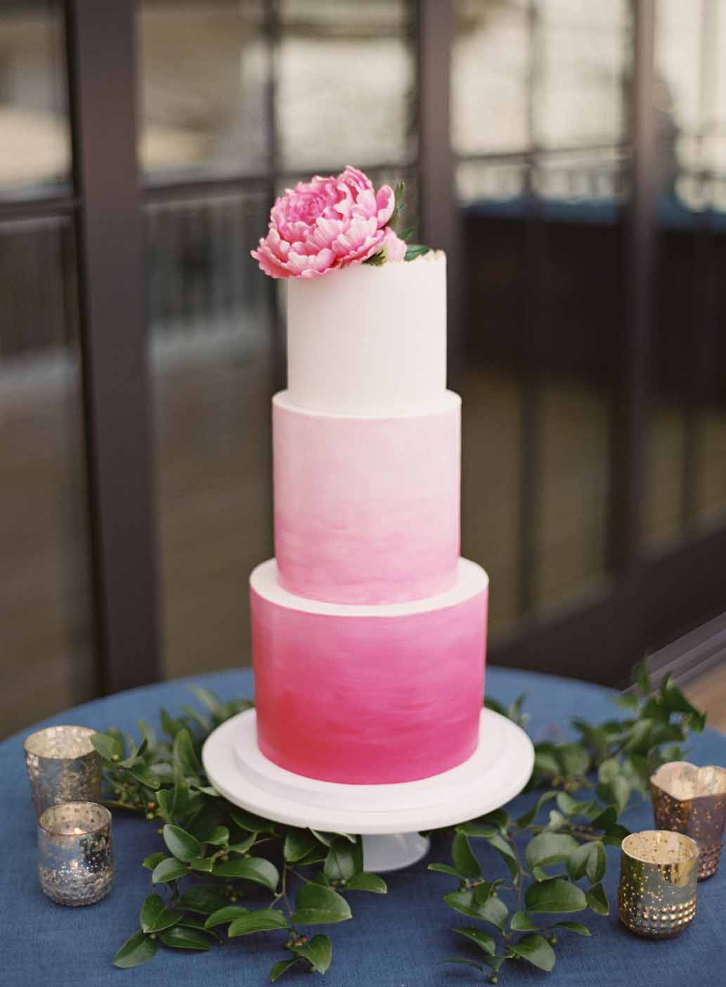 Pink ombre wedding cake topped with pink peony surrounded by greenery on a blue linen tablecloth at a hot pink and peach wedding at Roche Harbor Resort on Orcas Island