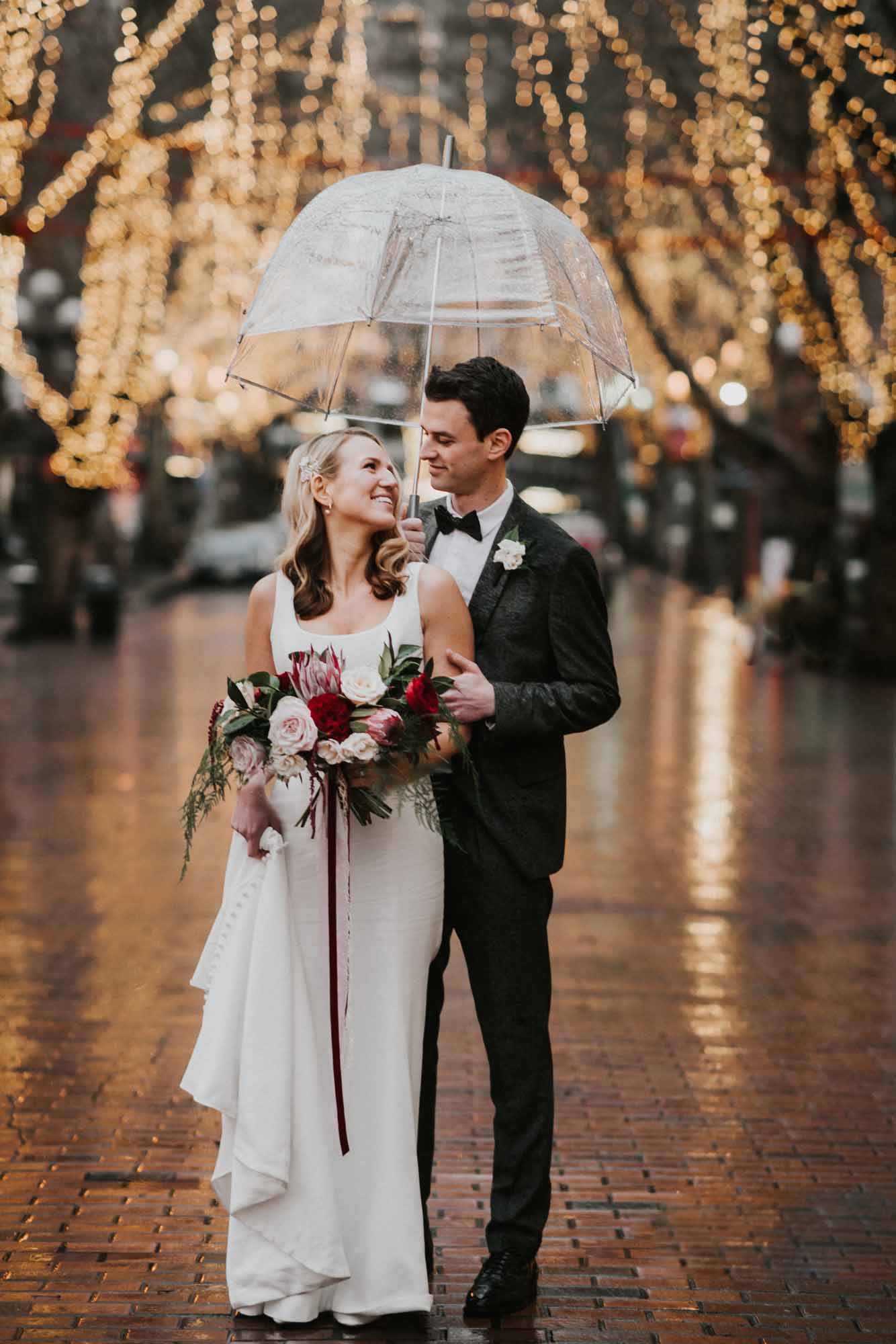bride and groom under an umbrella with lighted trees behind