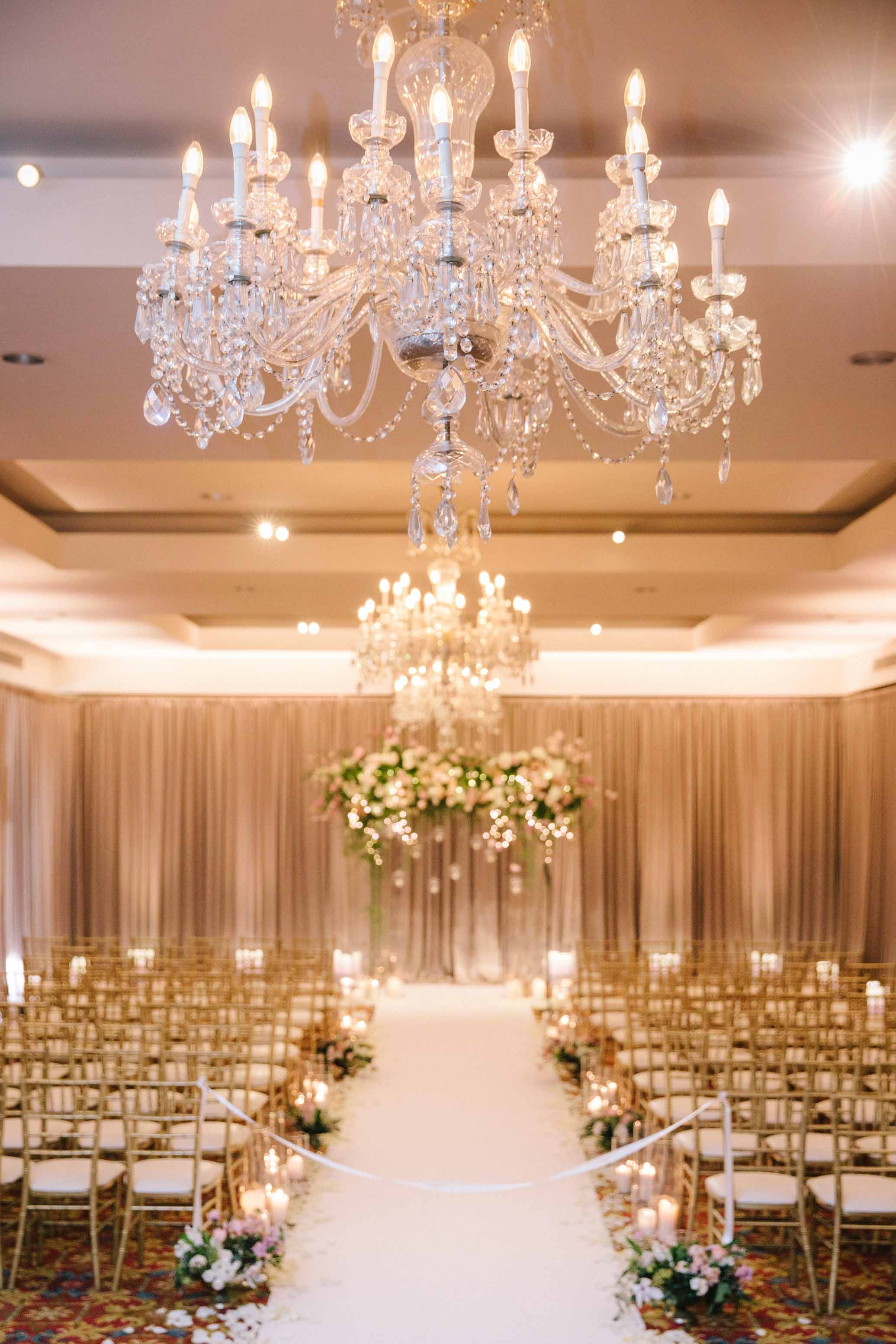 Wedding ceremony in hotel ballroom with crystal chandelier and rows of gold chairs