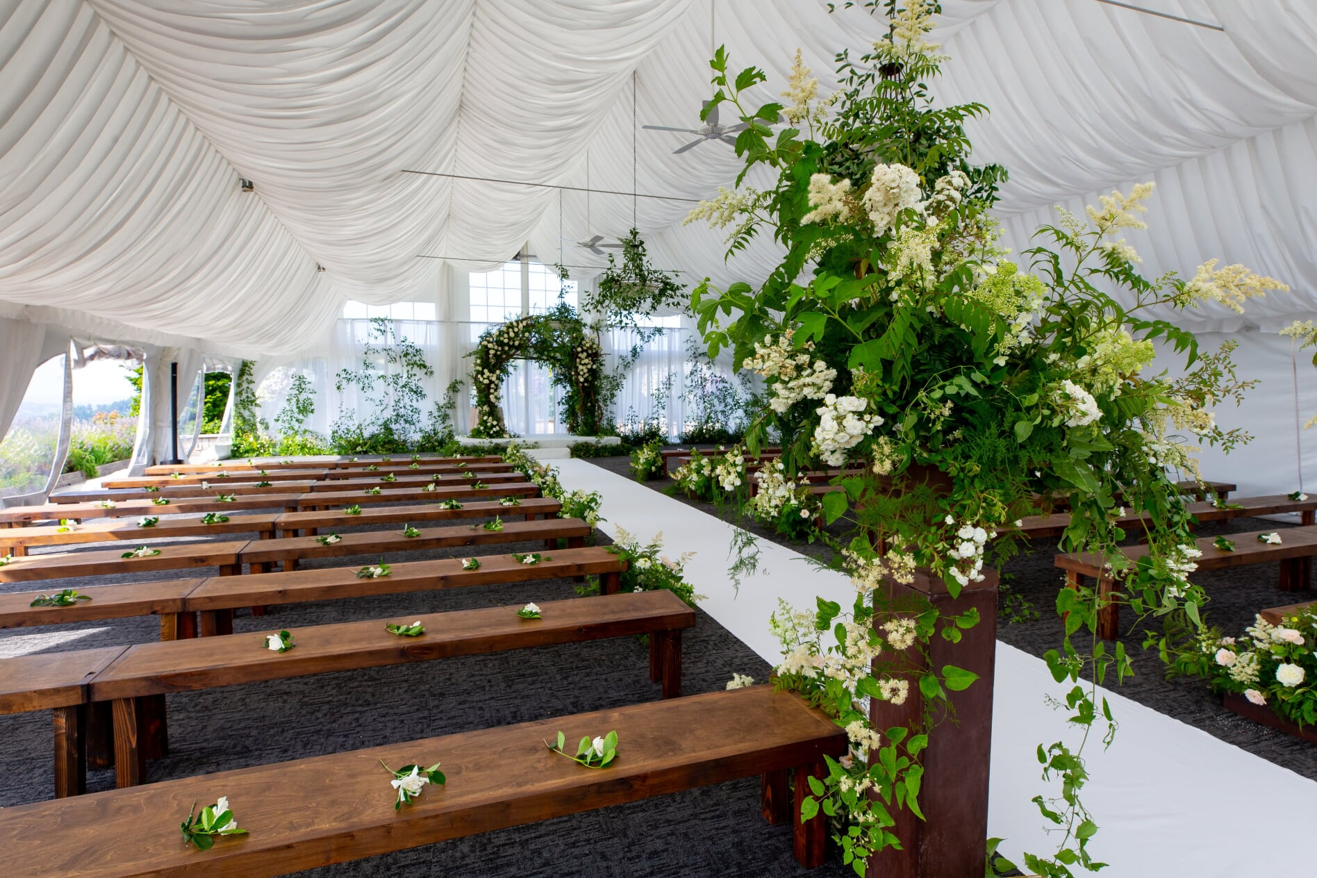 wooden benches for the ceremony in white tent with large floral urn and ceremony arch