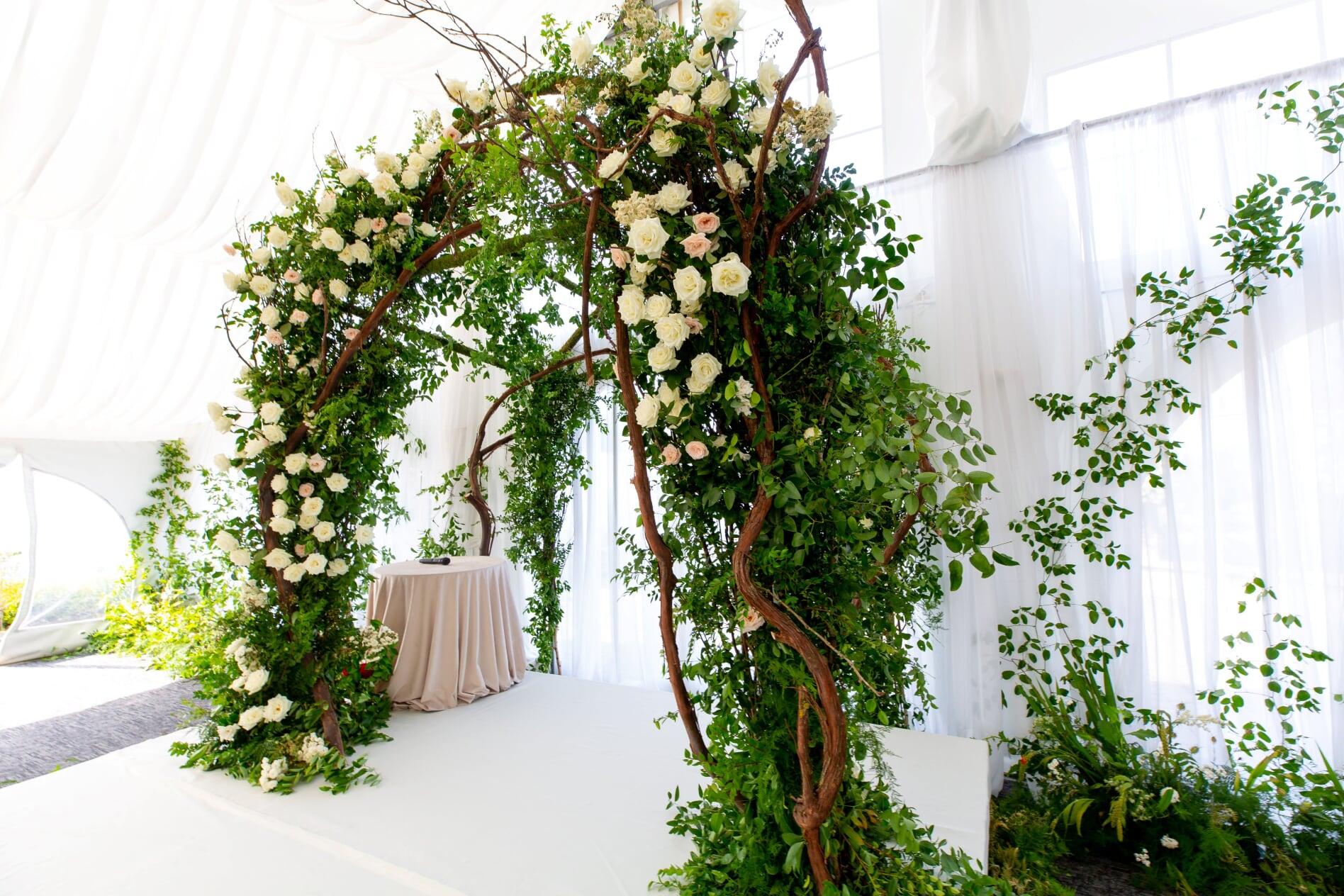 Grapevine ceremony arch with greenery and roses in this midsummer night's dream wedding