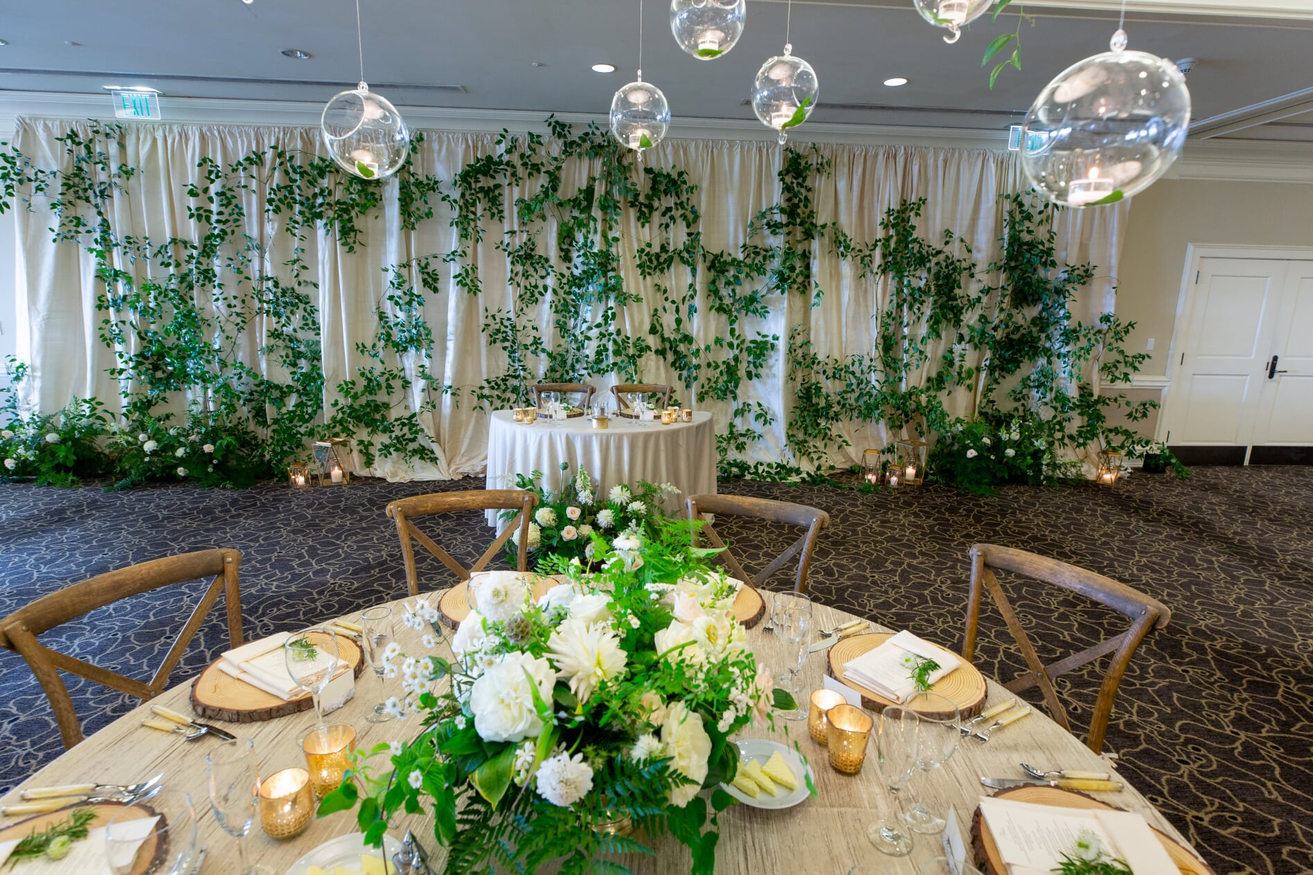 Sweetheart table with greenery backdrop, round table with white centerpiece