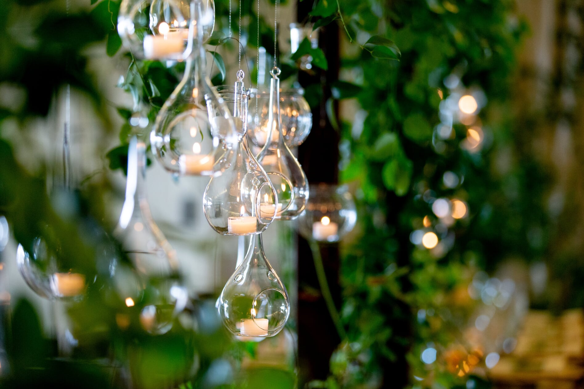hanging votives over reception table with greenery vines