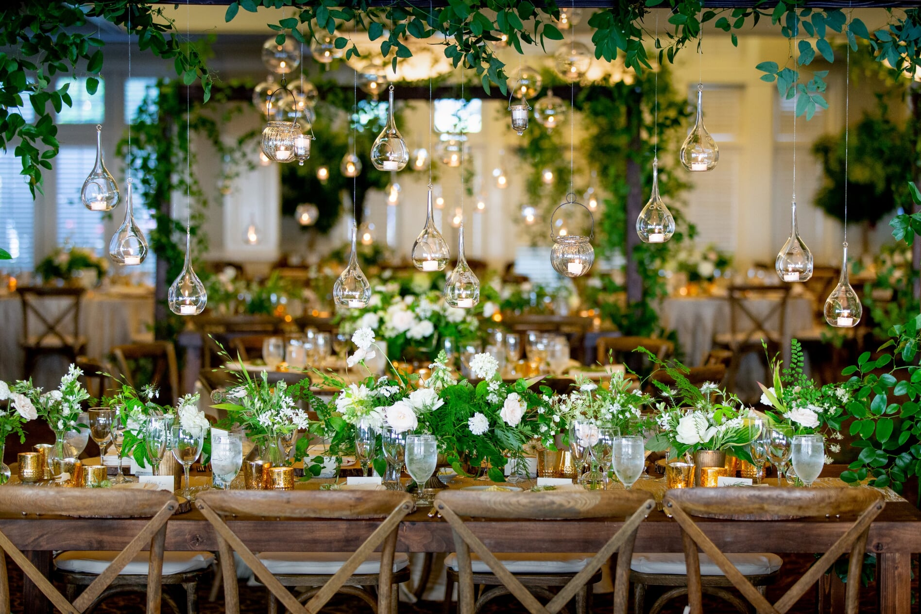 long wooden table with hanging candles and greenery at this Midsummer Night's Dream Wedding