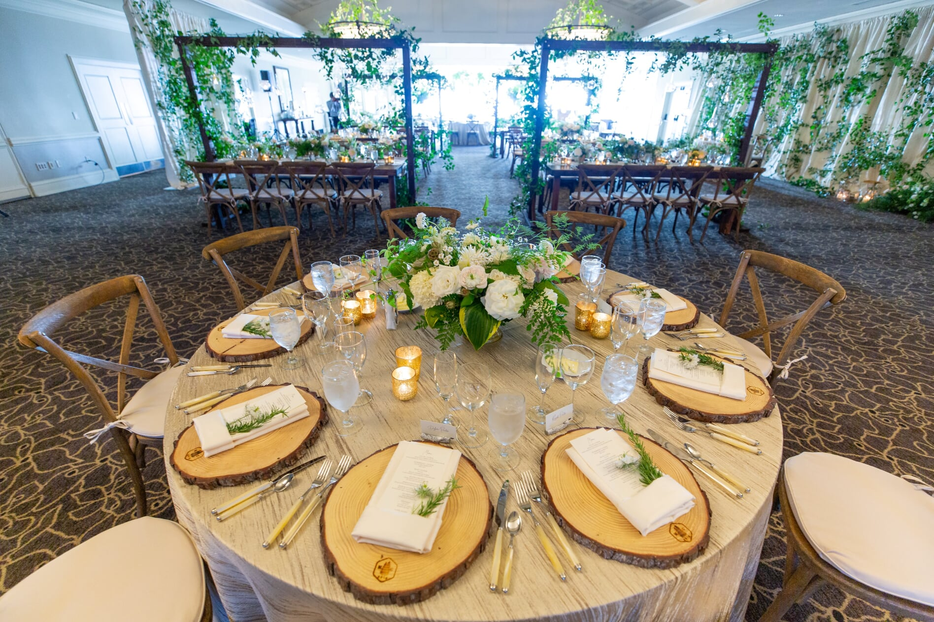 Round table at wedding reception with white and green centerpiece and wooden charger plates