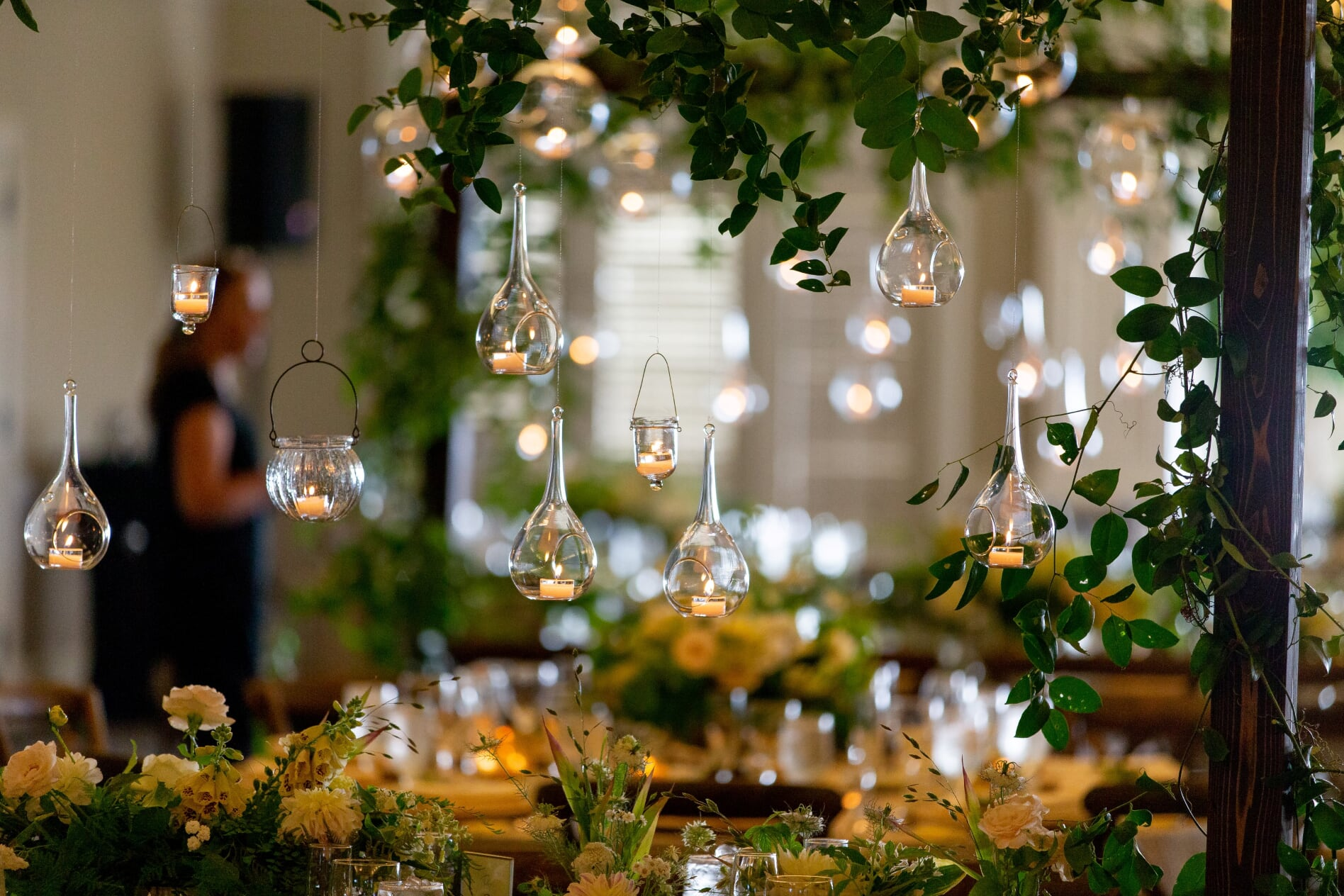 hanging candles and vines over wedding reception table