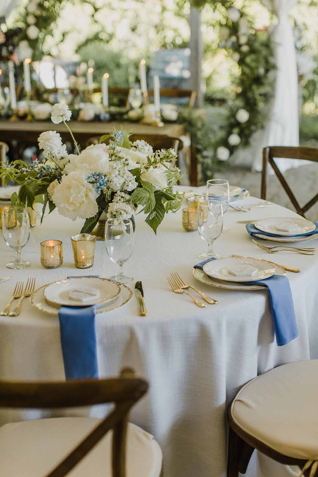 Cream and blue wedding reception table designed by Flora Nova, featuring gold compote arrangements.