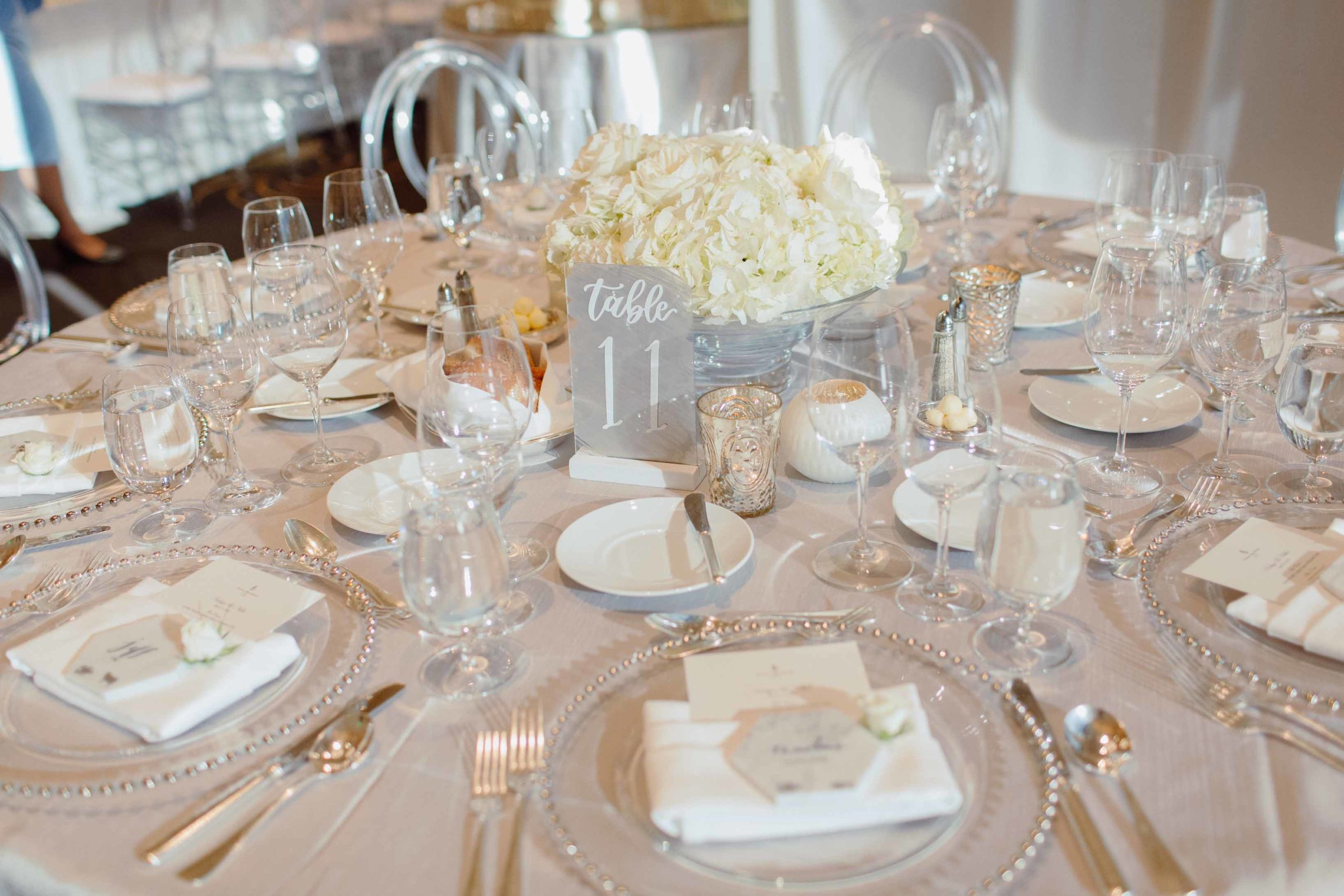 all white centerpiece with clear lucite chairs at wedding reception at the four seasons seattle