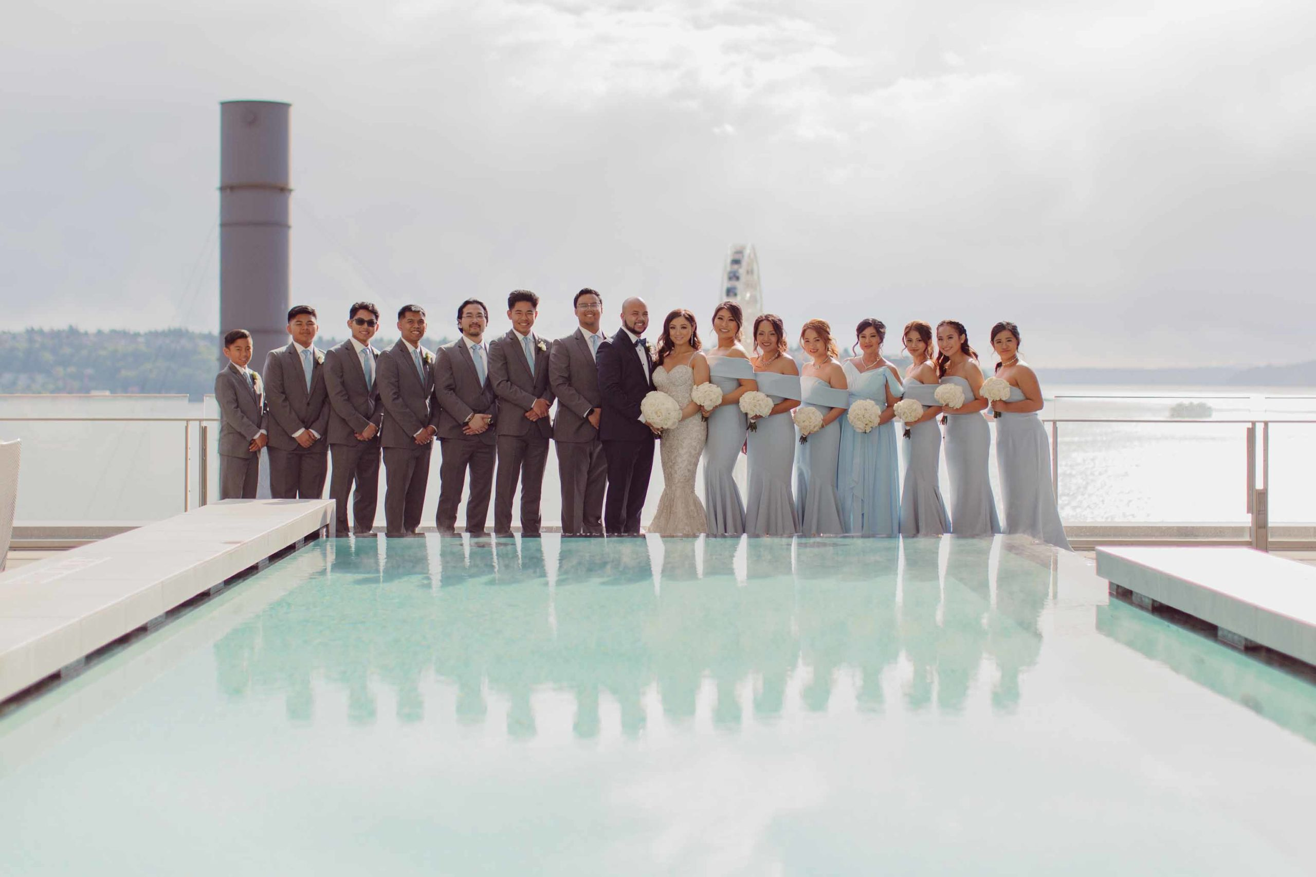 bridesmaids and groomsmen by infinity pool at the Four Seasons Seattle for all white wedding