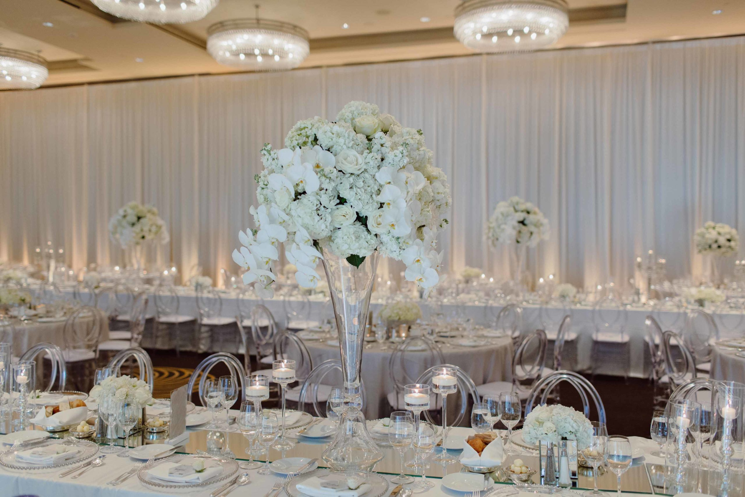 tall all white centerpeice on crystal vase with white phalenopsis orchids at wedding reception at four seasons seattle