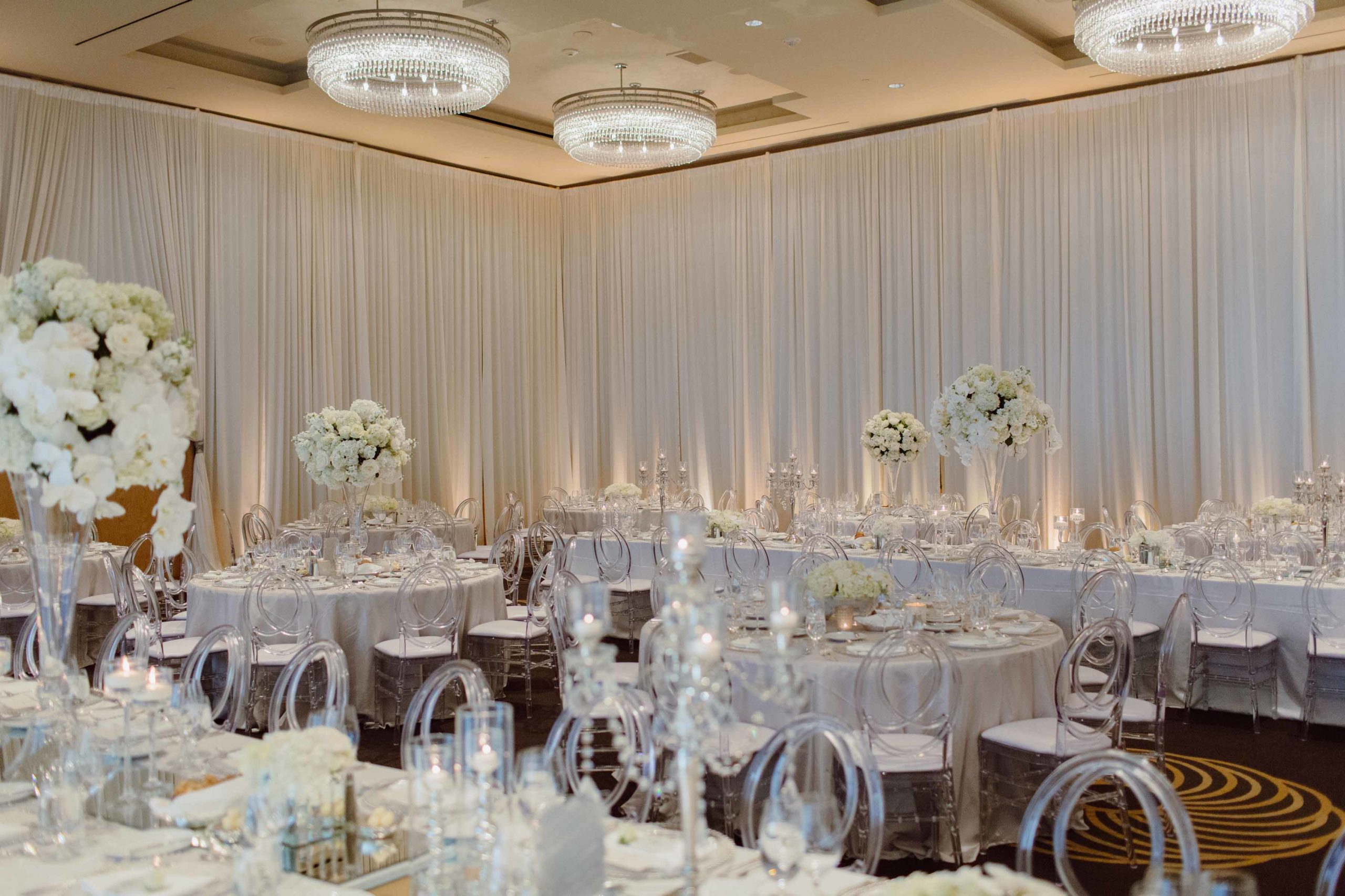 white draped ballroom at the four seasone hotel seattle with clear lucite chairs and white centerpeices