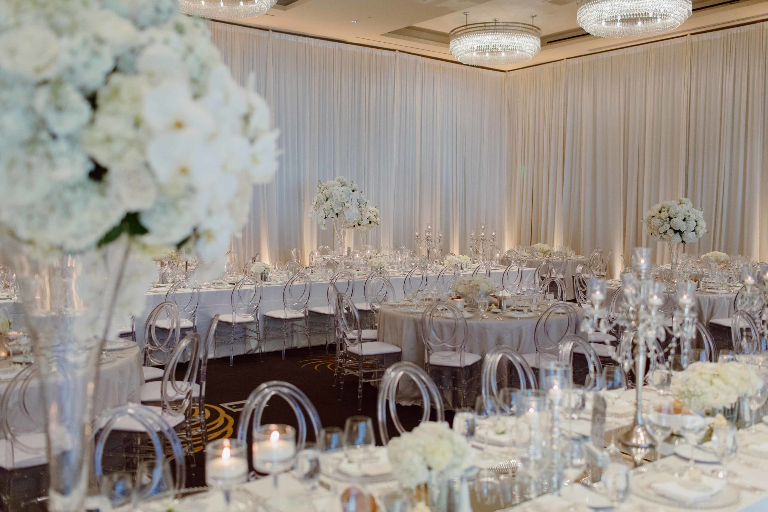 all white wedding reception with draped ballroom, clear lucite chairs, and tall white centerpeices with phalenopsis orchids