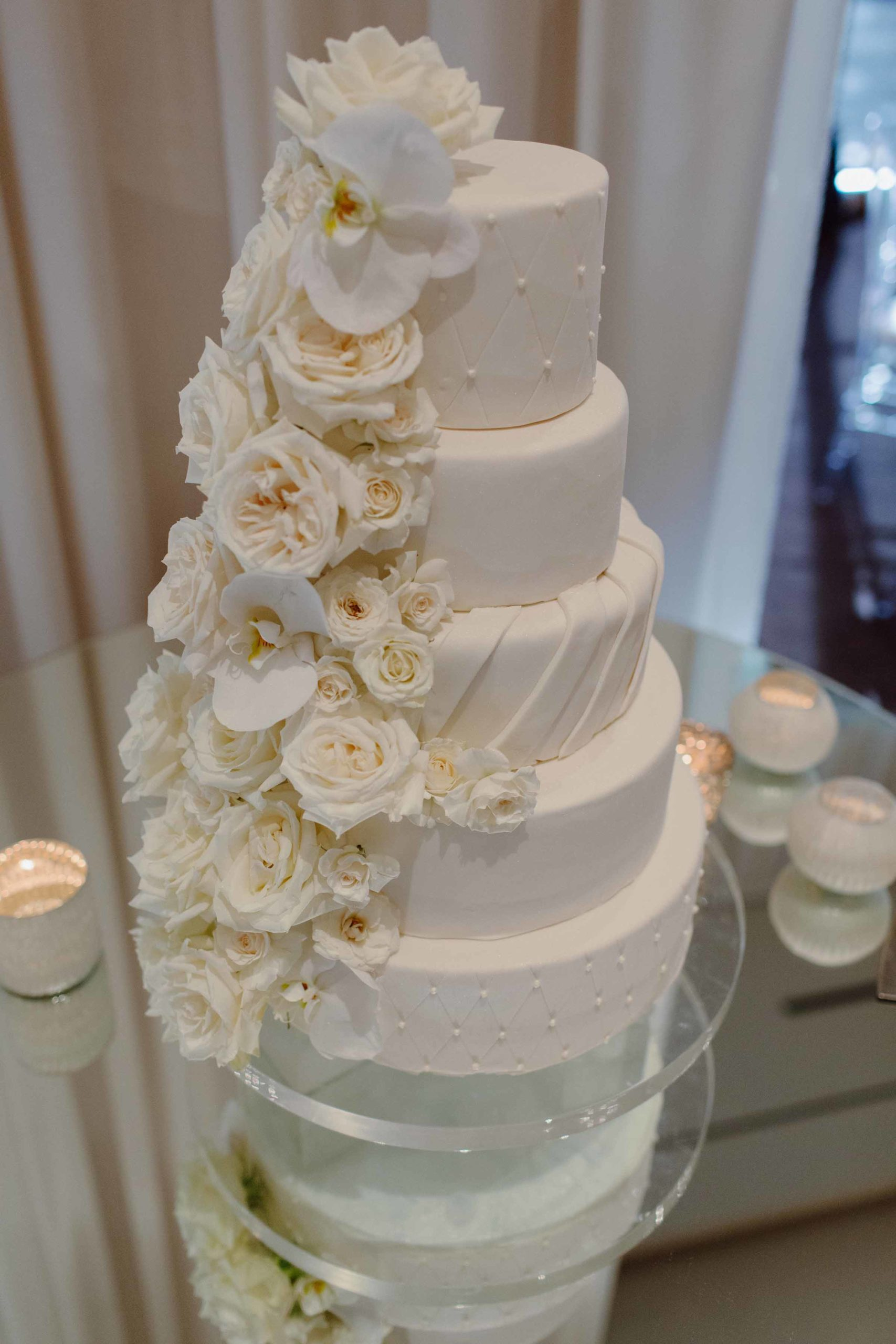 all white cake with cascade of white roses
