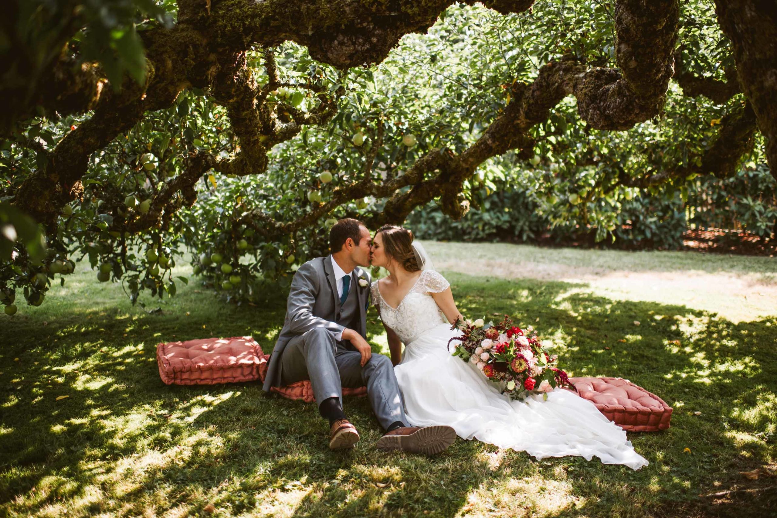 Kissing under the apple trees in the brides family orchard on their wedding day at an intimate summer garden wedding on Lake Washington.