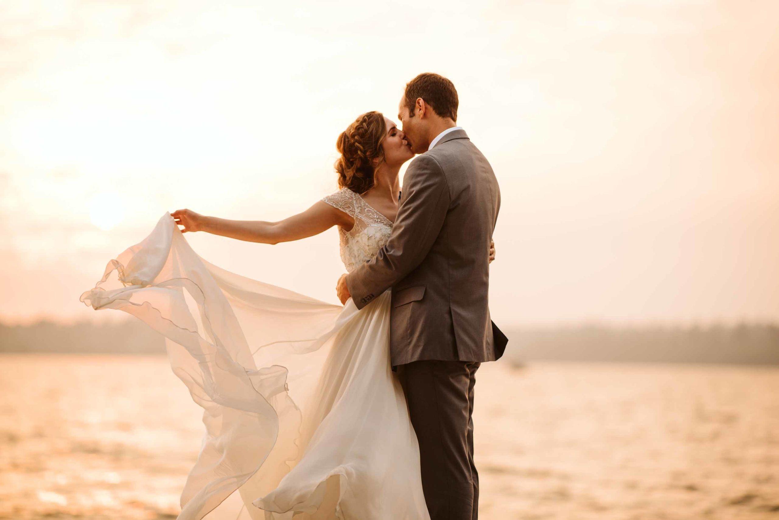 Romantic sunset kiss between bride and groom beside Lake Washington