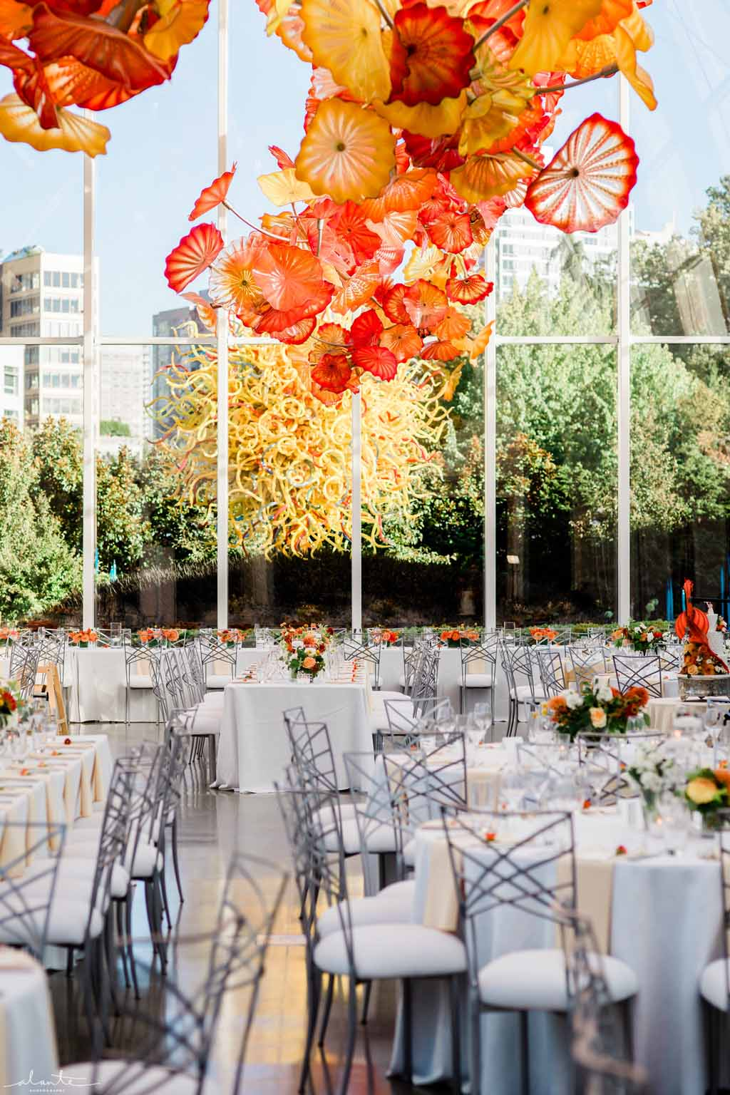 Orange summer wedding reception at Chihuly Garden and Glass, white linen tables with vibrant orange floral centerpieces | Flora Nova Design Seattle