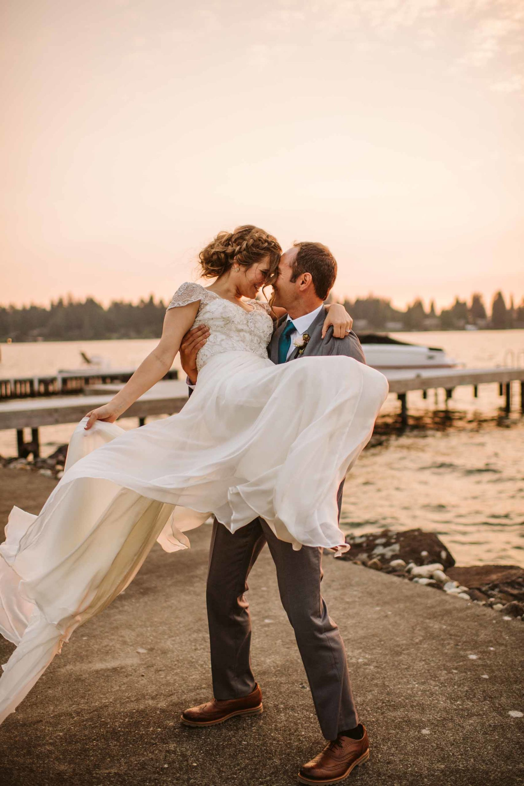 Romantic sunset wedding portrait on Lake Washington with groom carrying his bride on the dock.