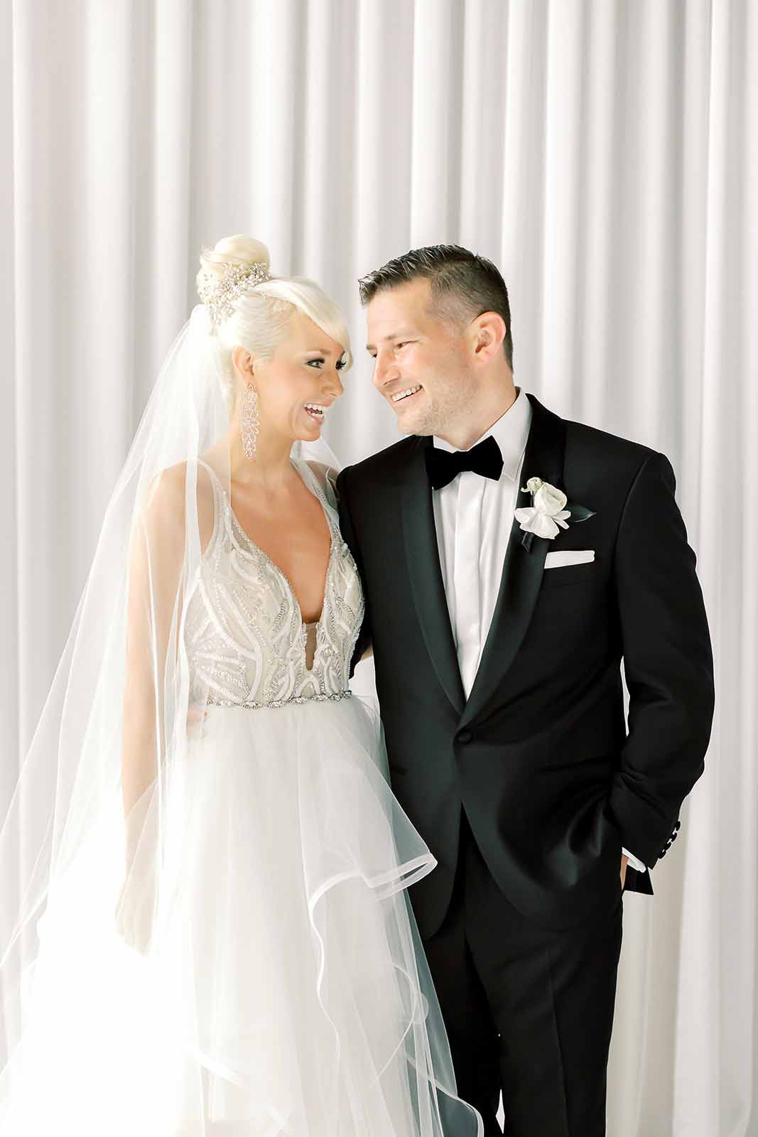Bride and groom smiling at each other on the day of their wedding, groom in a tux and bride with a veil and a formal ballgown dress