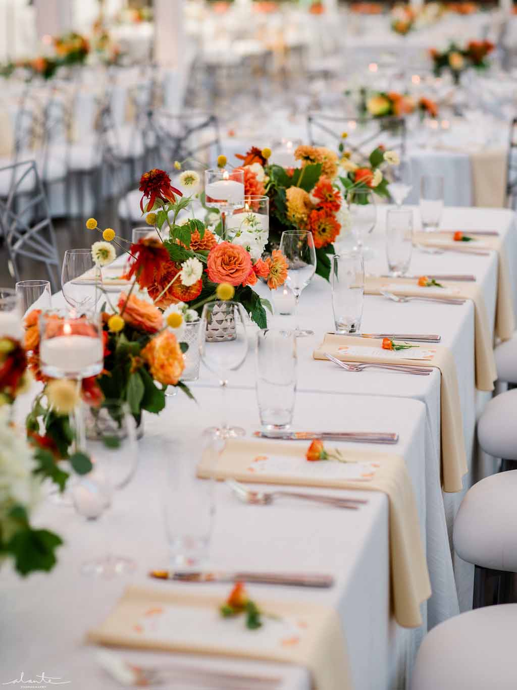 Long rectangle reception tables lined with vibrant orange summer flowers in low vases.