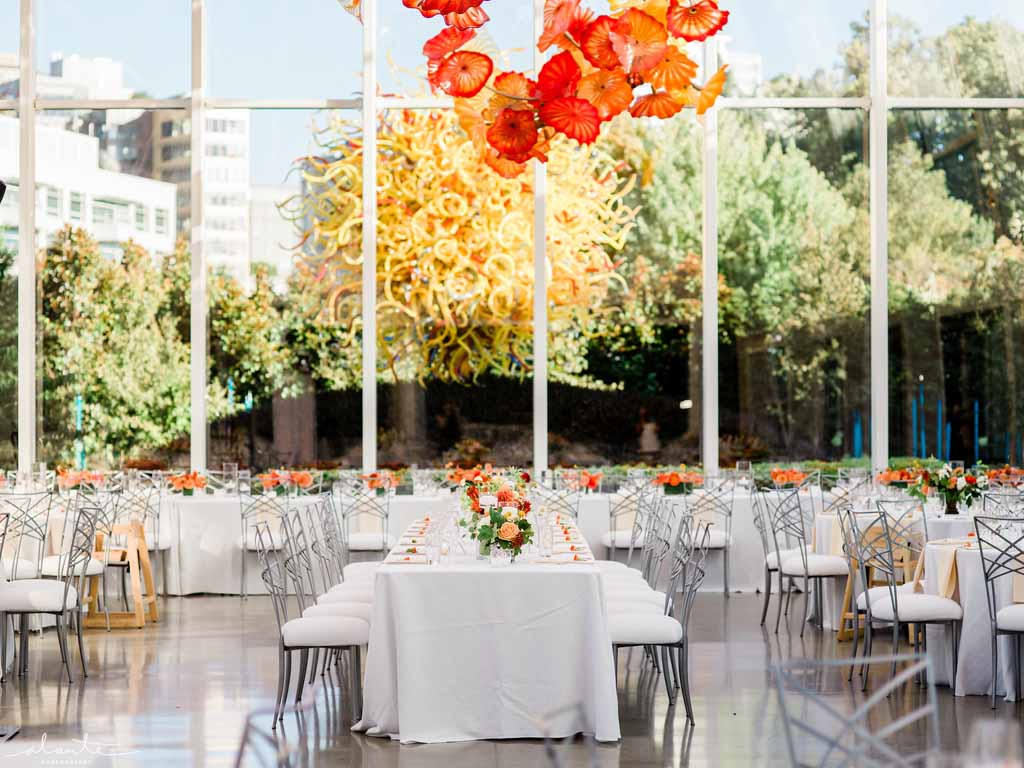 Orange wedding reception at Chihuly Seattle with long tables with white linens and chameleon chairs  | Flora Nova Design