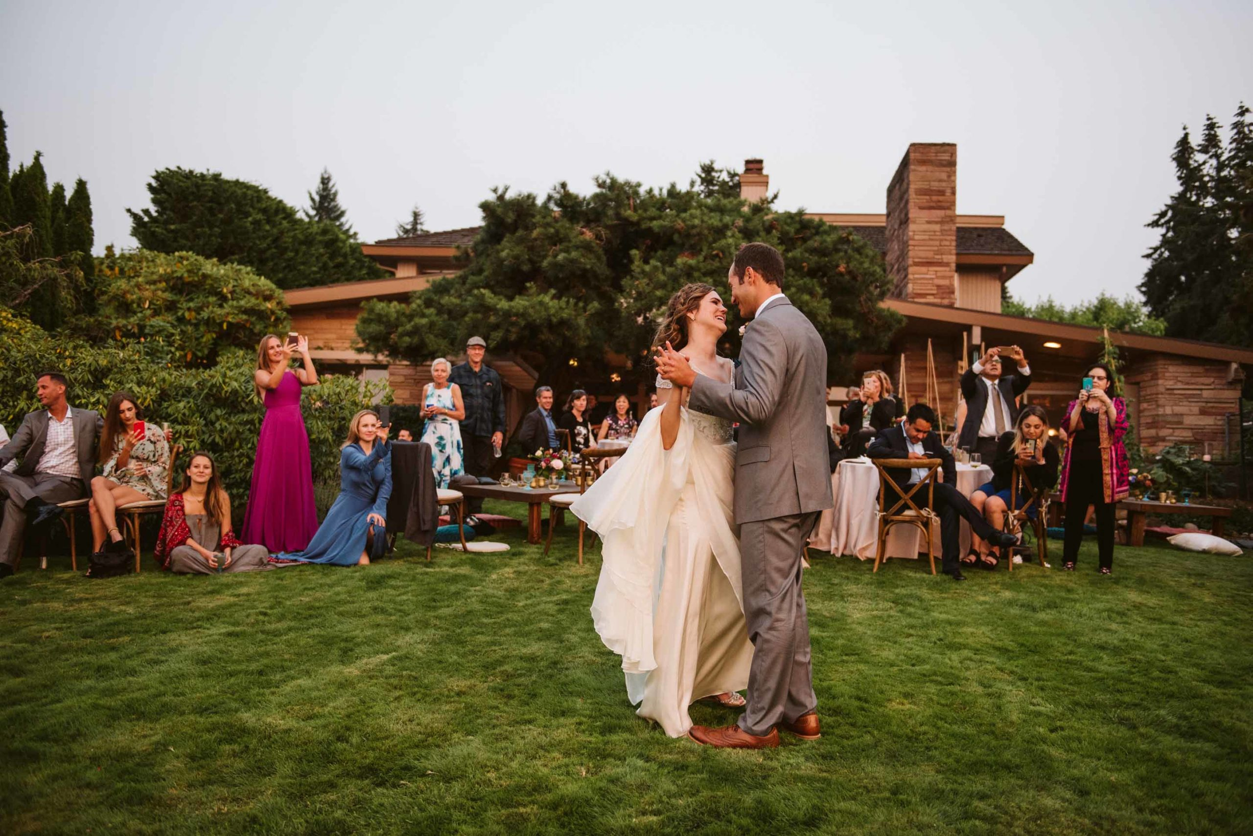 Bride and groom's first dance on the lawn of the backyard where they held their summer wedding