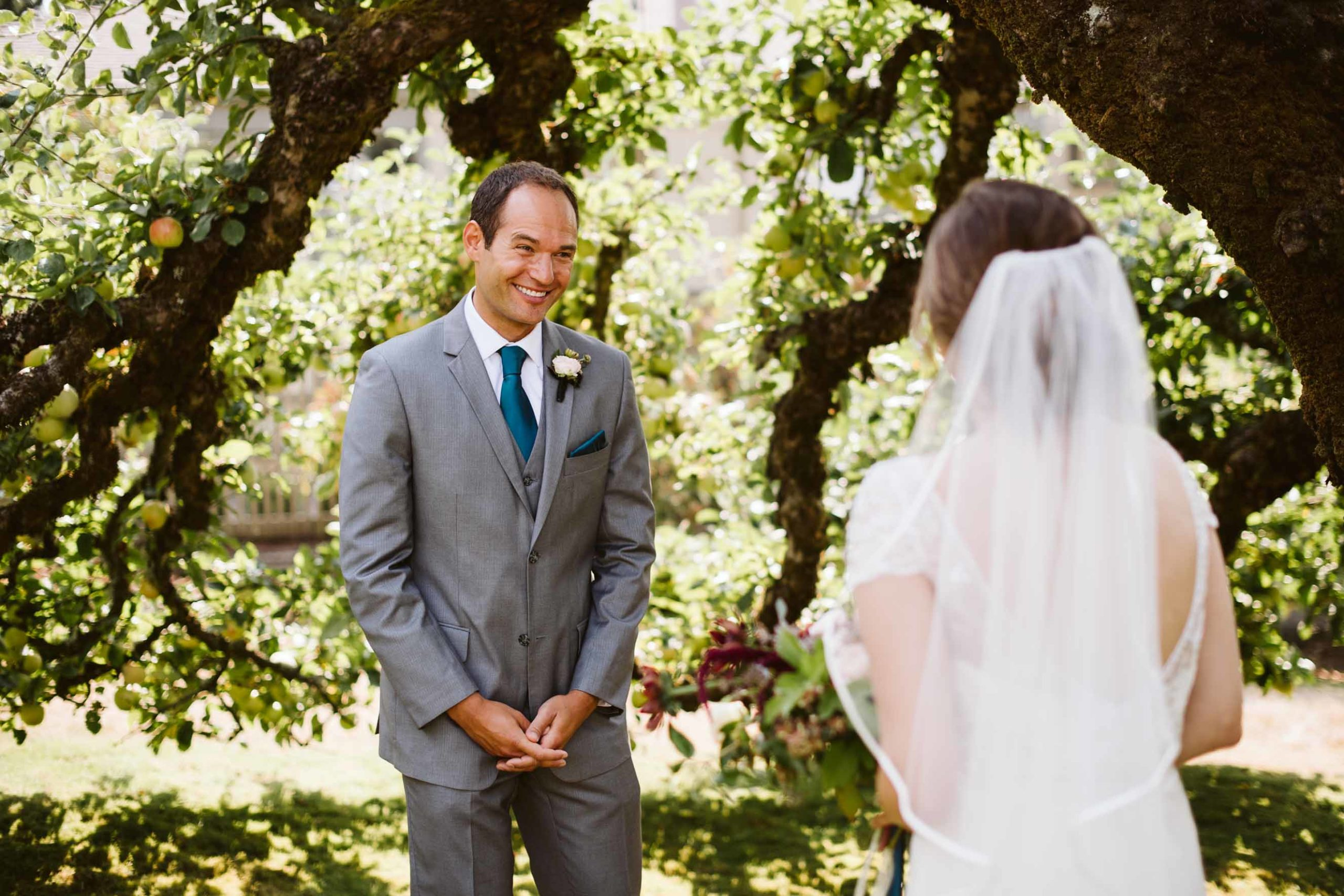 Grooms first look at his bride in an orchard on Lake Washington