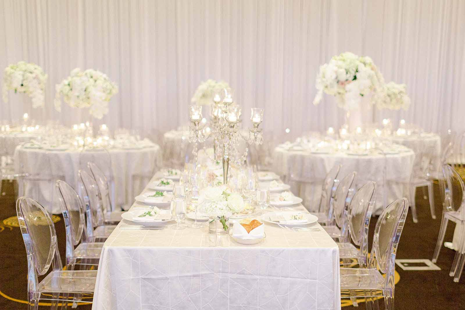 Long white reception table with low white floral centerpieces and candelabras in the Four Seasons Ballroom