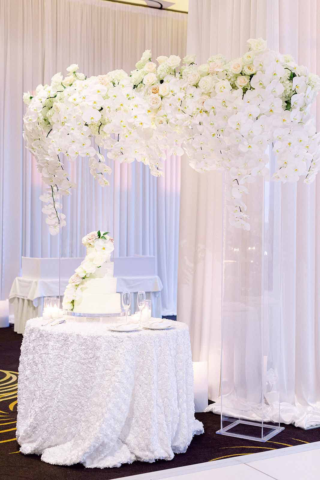 White tired wedding cake with waterfall of fresh floral under a lucite arch covered in white orchids designed by Flora Nova Design Seattle