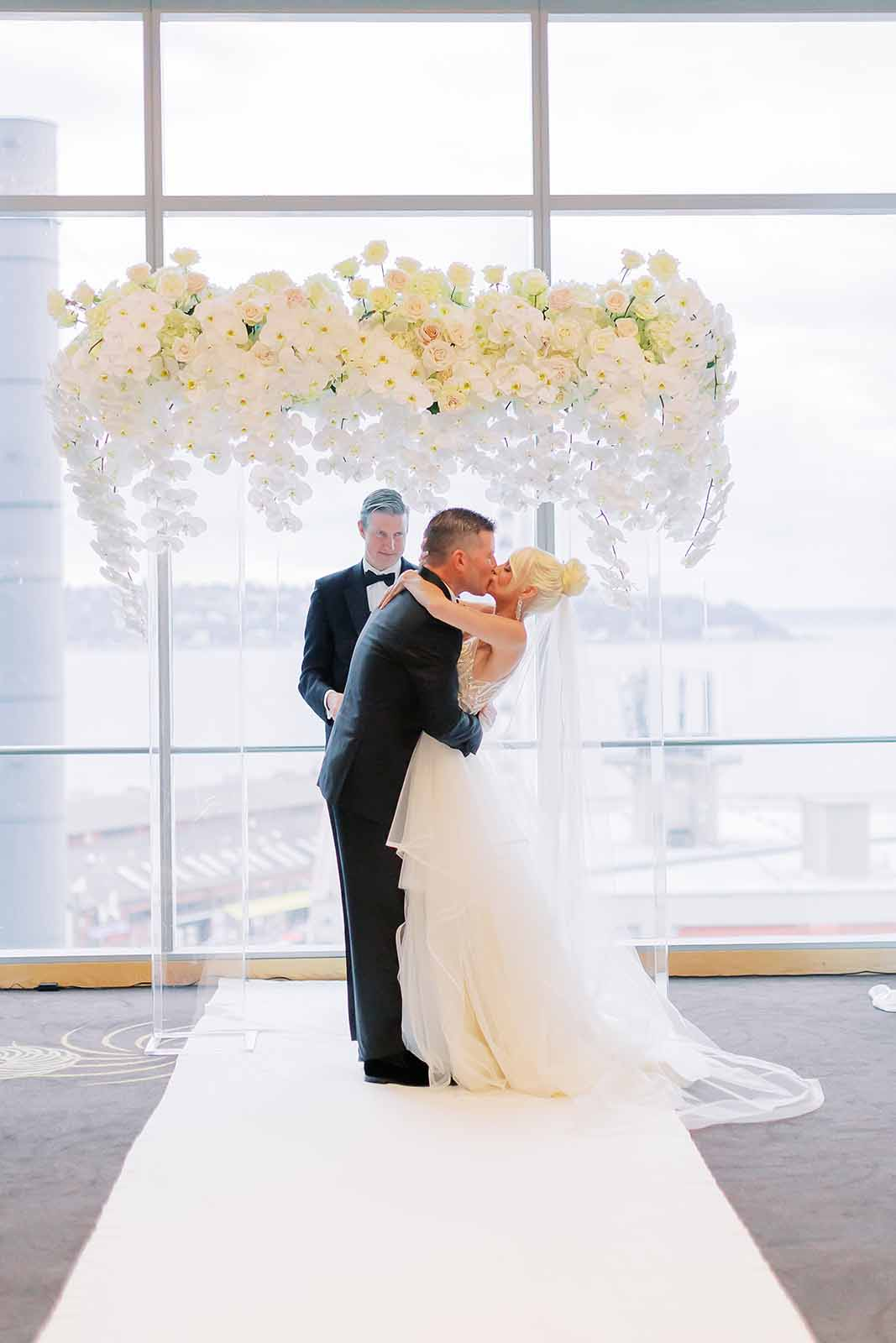 Bride and Groom kissing in front of a white floral arch covered in orchids during their formal ballroom wedding ceremony
