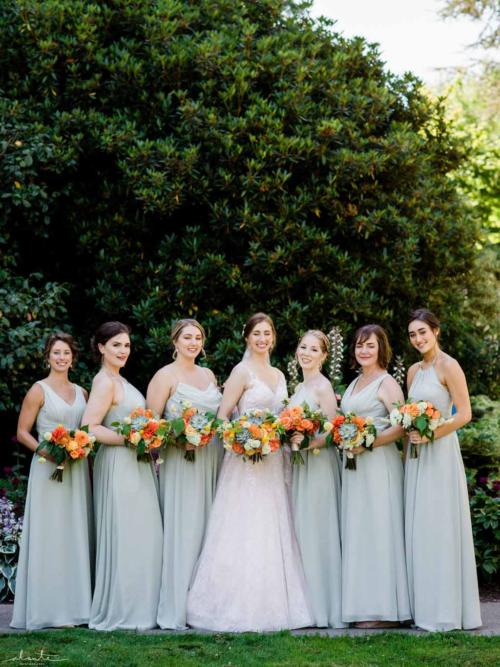 Bridal party in mint dresses for an orange summer wedding at Chihuly Gardens Seattle.