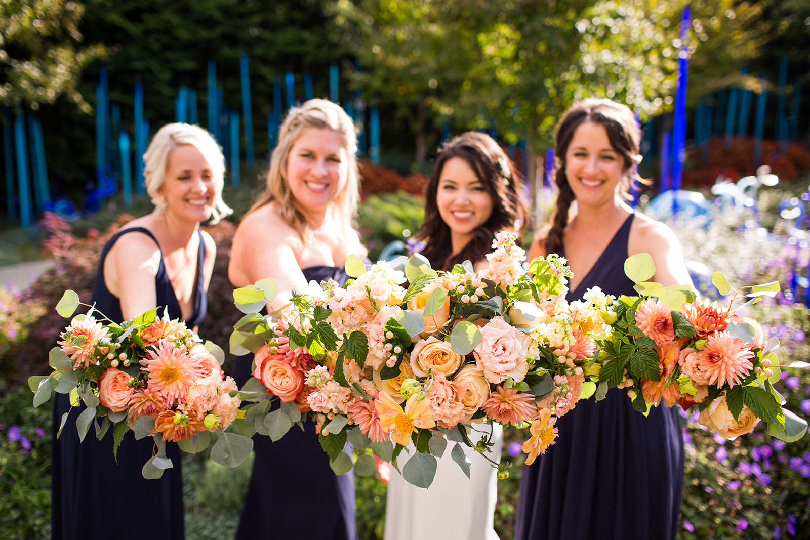 Bride and bridesmaids holding peach and coral bouquets with fall flowers | Flora Nova Design Seattle