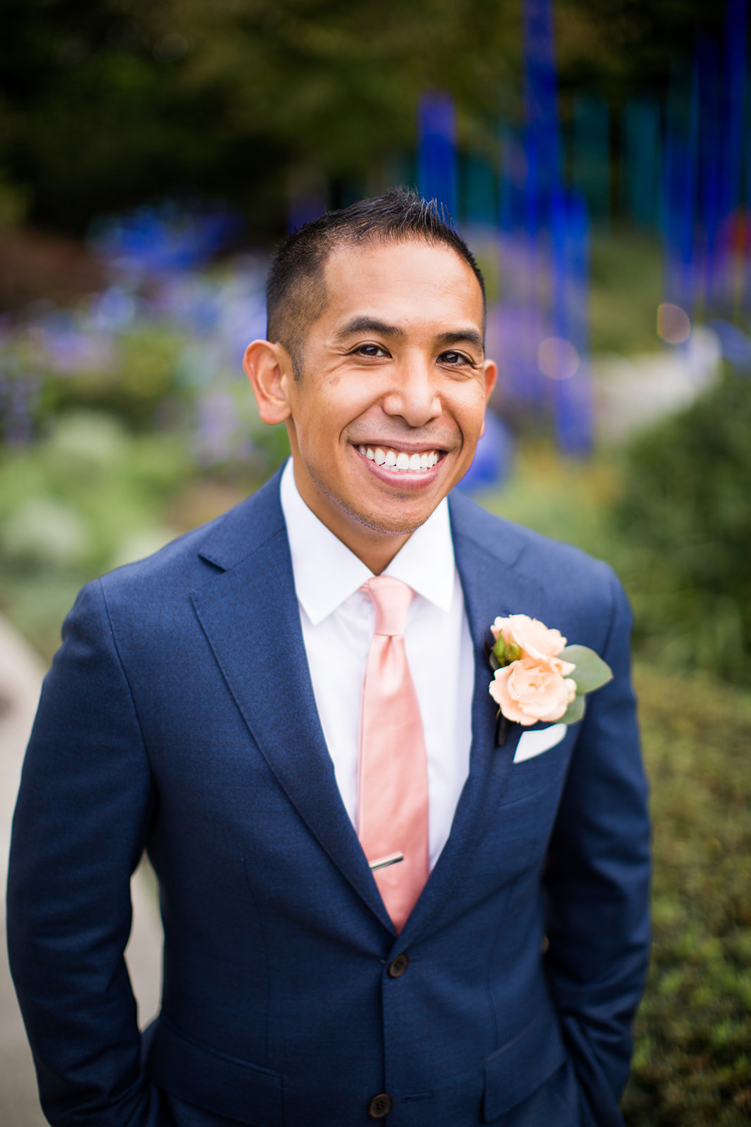 Smiling groom with a peach rose boutonniere waiting for his fall navy blue and burnt orange wedding at Chihuly | Flora Nova Design Seattle