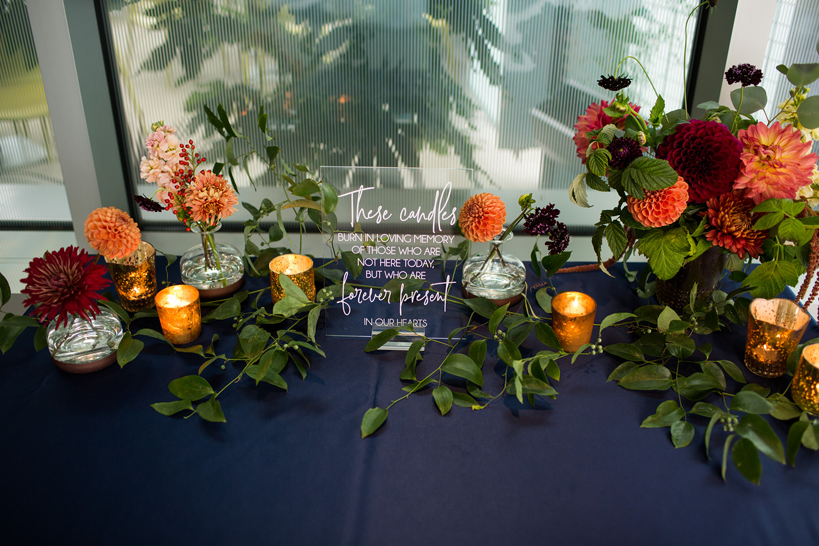 Table at fall wedding decorated with gold votive candles and fall flower arrangements