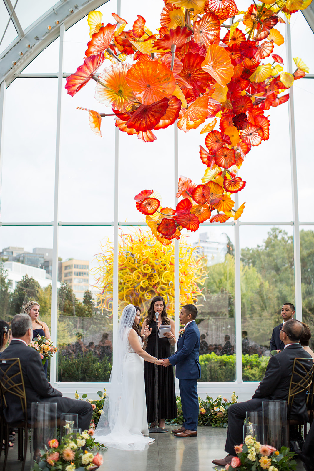 Fall wedding ceremony in the glass house at Chihuly, bride and groom surrounded by wedding guests