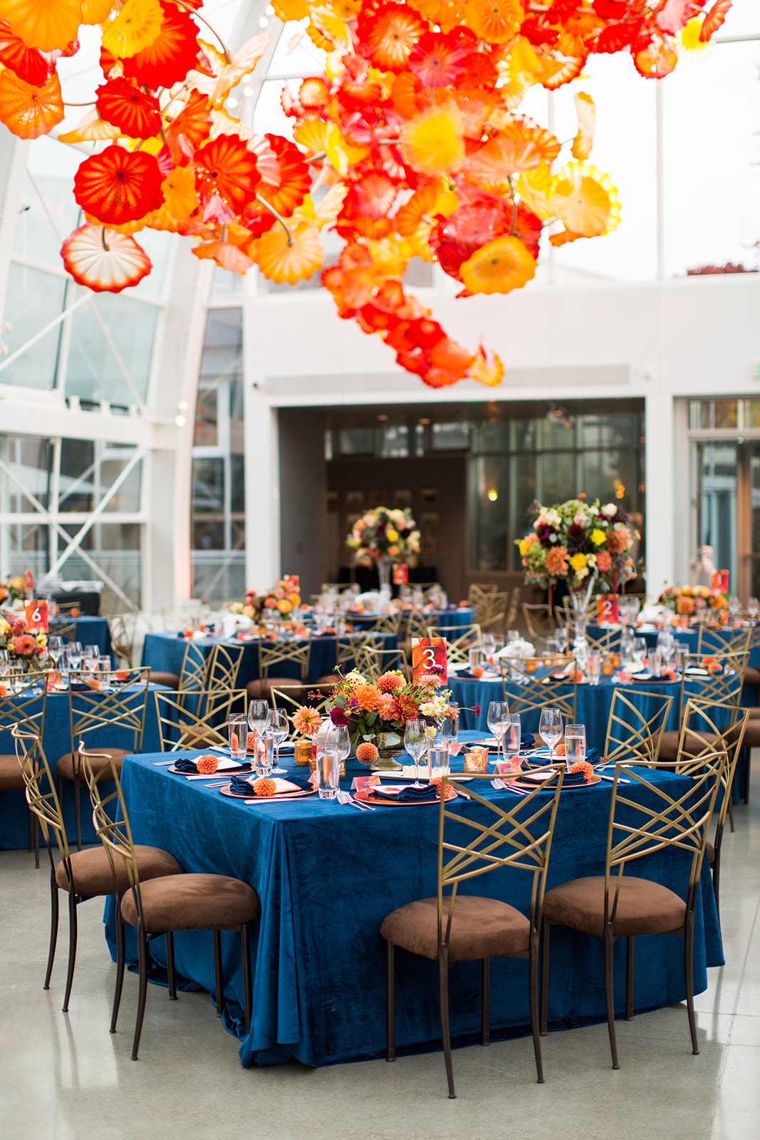 Navy blue and burnt orange wedding reception with navy velvet linens and fall floral centerpieces in orange and grey floral designed by Flora Nova Design Seattle